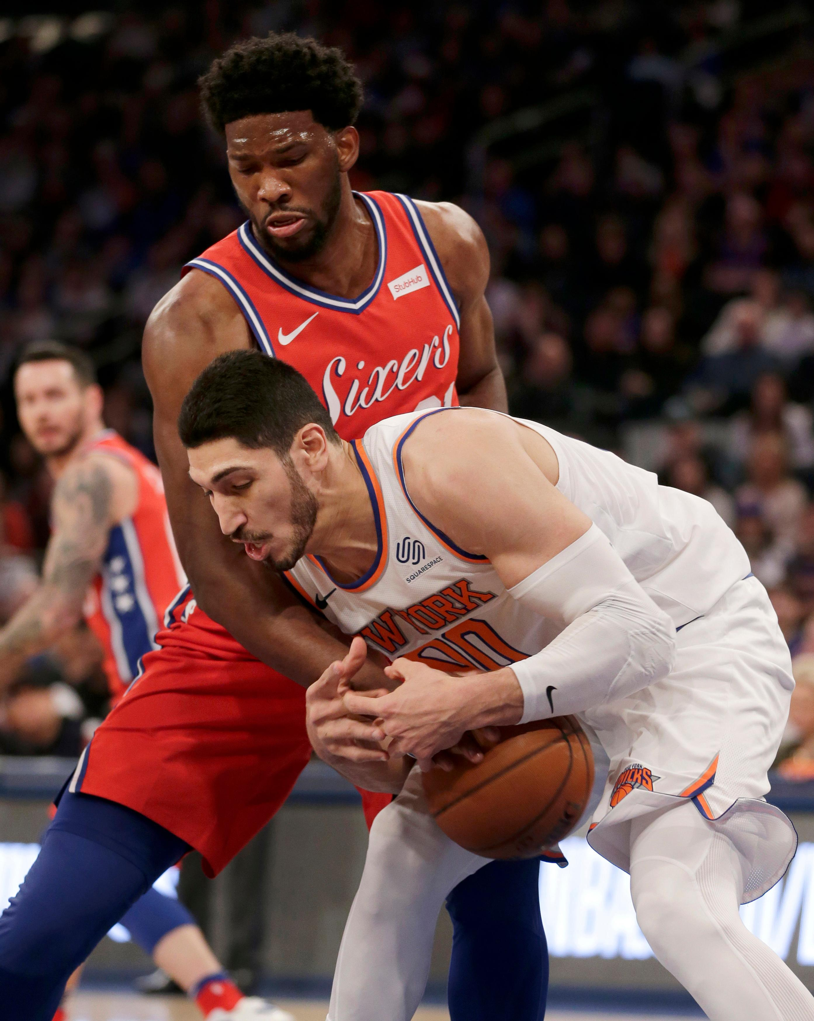 Philadelphia 76ers' Joel Embiid, top, and New York Knicks' Enes Kanter fight for a loose ball during the first half of the NBA basketball game, Monday, Dec. 25, 2017, in New York. (AP Photo/Seth Wenig)