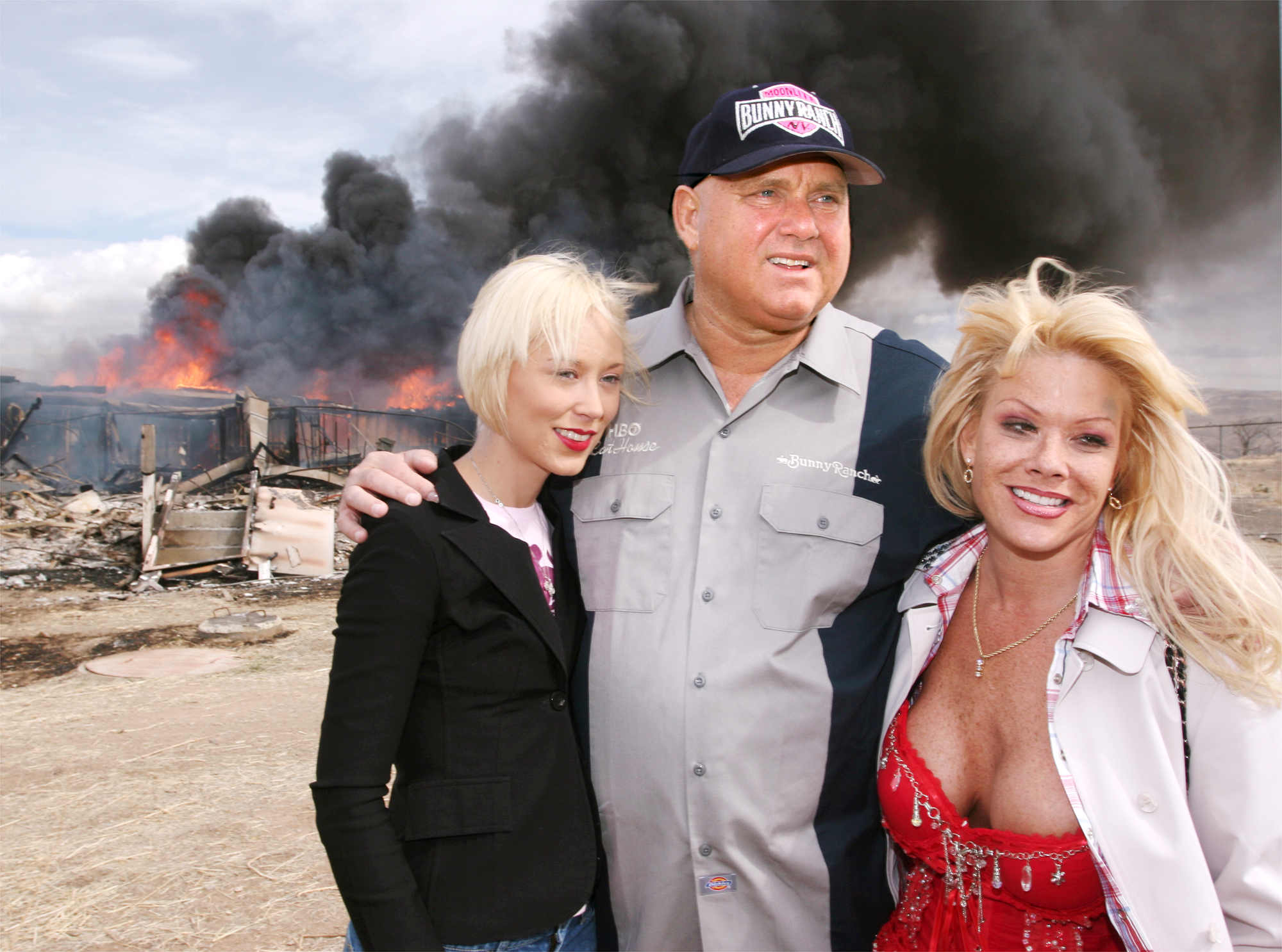 "Moonlite Bunnyranch brothel owner Dennis Hof poses with two of his ""working girls"" Brooke Taylor, left, and a woman working under the name ""Airforce Amy"", right, as firefighters burn down remains of the former Mustang Ranch 2 brothel east of Reno, Nevada (AP Photo/Debra Reid)"