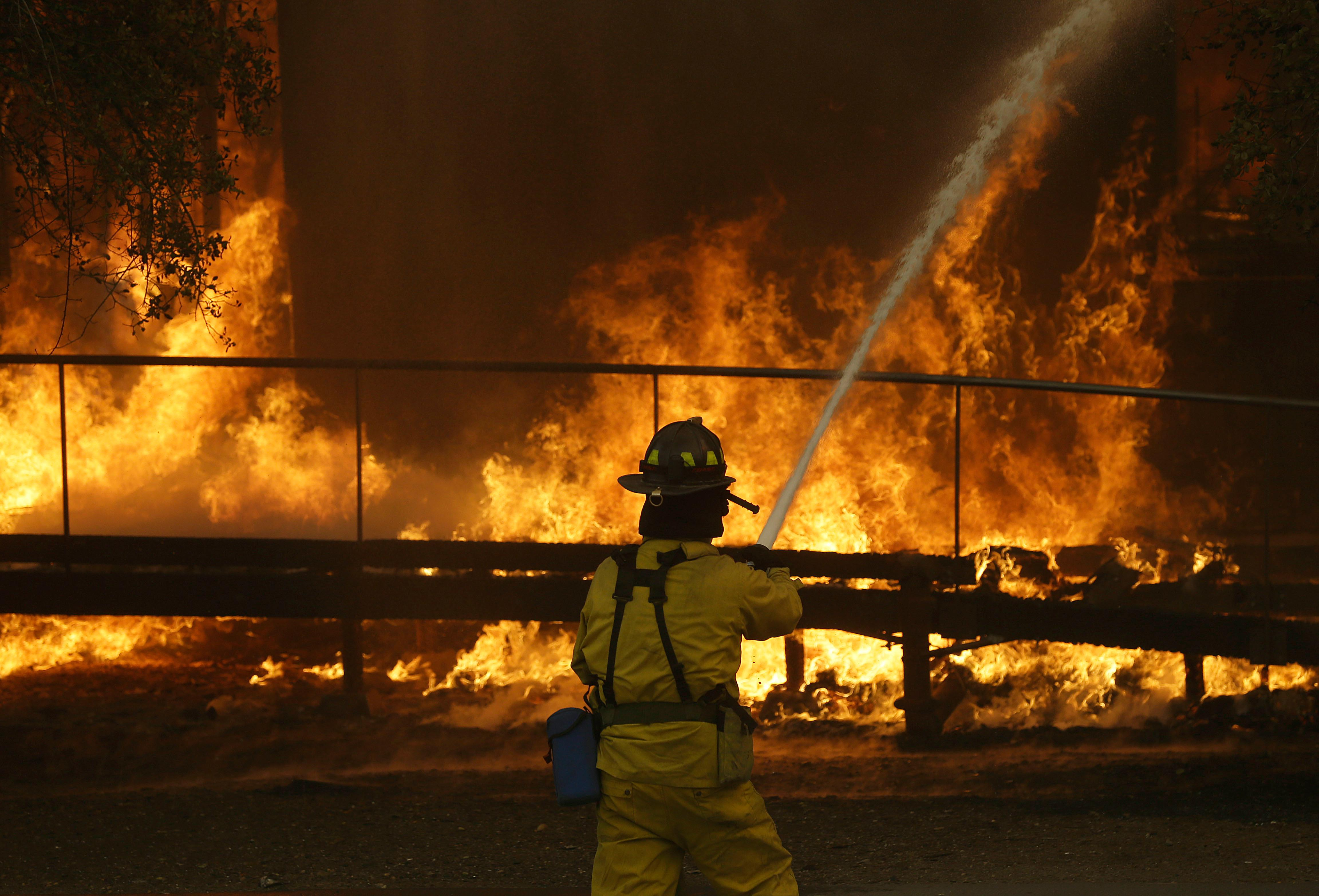 FILE - In this Oct. 9, 2017 file photo, a firefighter sprays a hose into a Keysight Technologies building in Santa Rosa, Calif. The Santa Rosa Press Democrat reported that more than 100 boxes of letters and other materials from tech pioneers William Hewlett and David Packard burned in the fires. Electronics firm Keysight Technologies had acquired the archives through spinoffs, and the archives were stored at its offices in Santa Rosa. (AP Photo/Jeff Chiu, file)