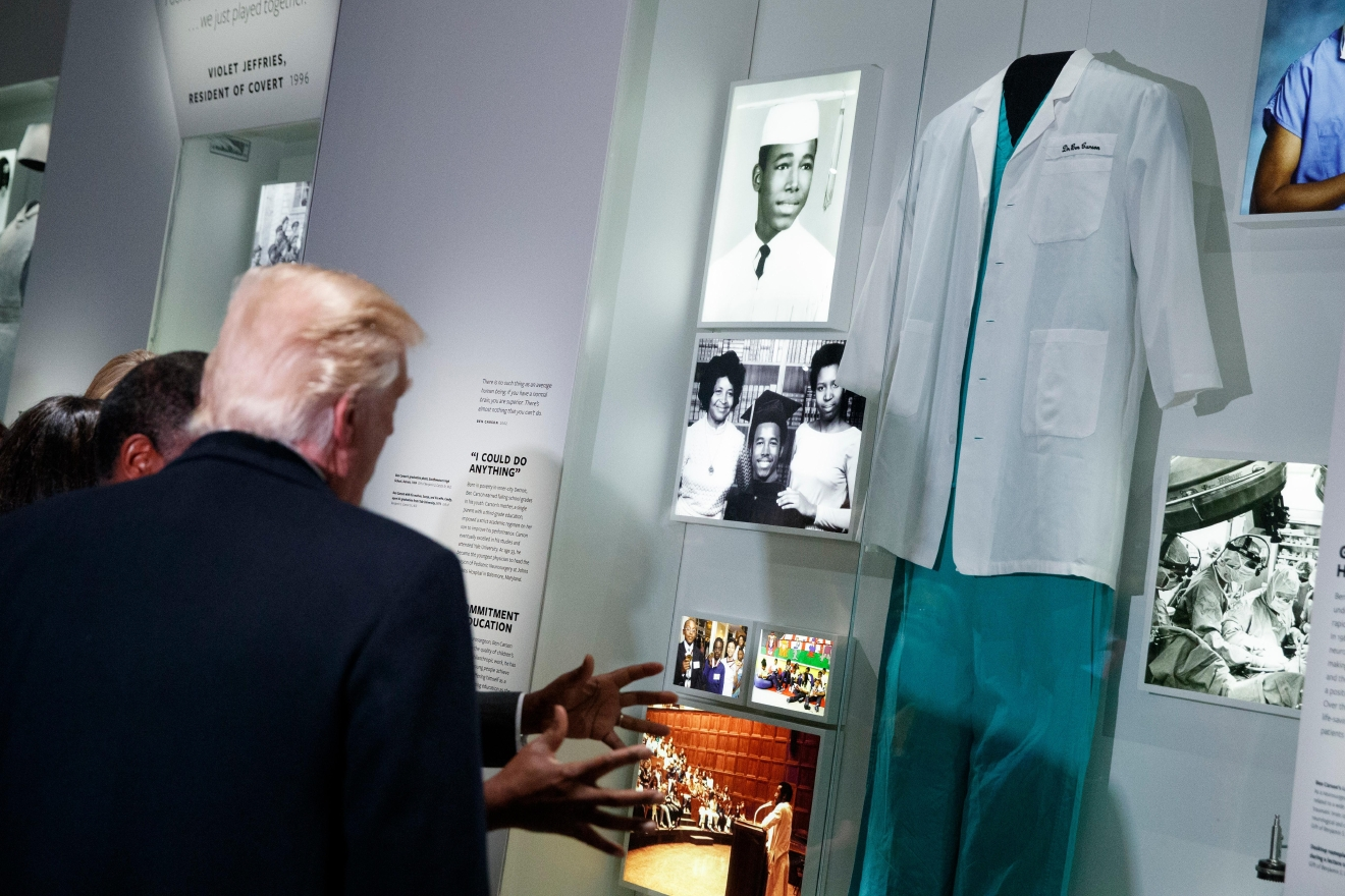 President Donald Trump looks at an exhibit of Dr. Ben Carson, his nominee for Housing and Urban Development secretary, during a tour of the National Museum of African American History and Culture, Tuesday, Feb. 21, 2017, in Washington. (AP Photo/Evan Vucci)