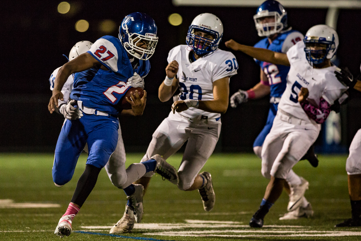 Churchill Lancers running back Sam Jackson (#27) tries to pull away from Eagle Point free safety Coldin Shopp (#11). Eagle Point defeated Churchill 42-37.  Photo by Austin Hicks, Oregon News Lab