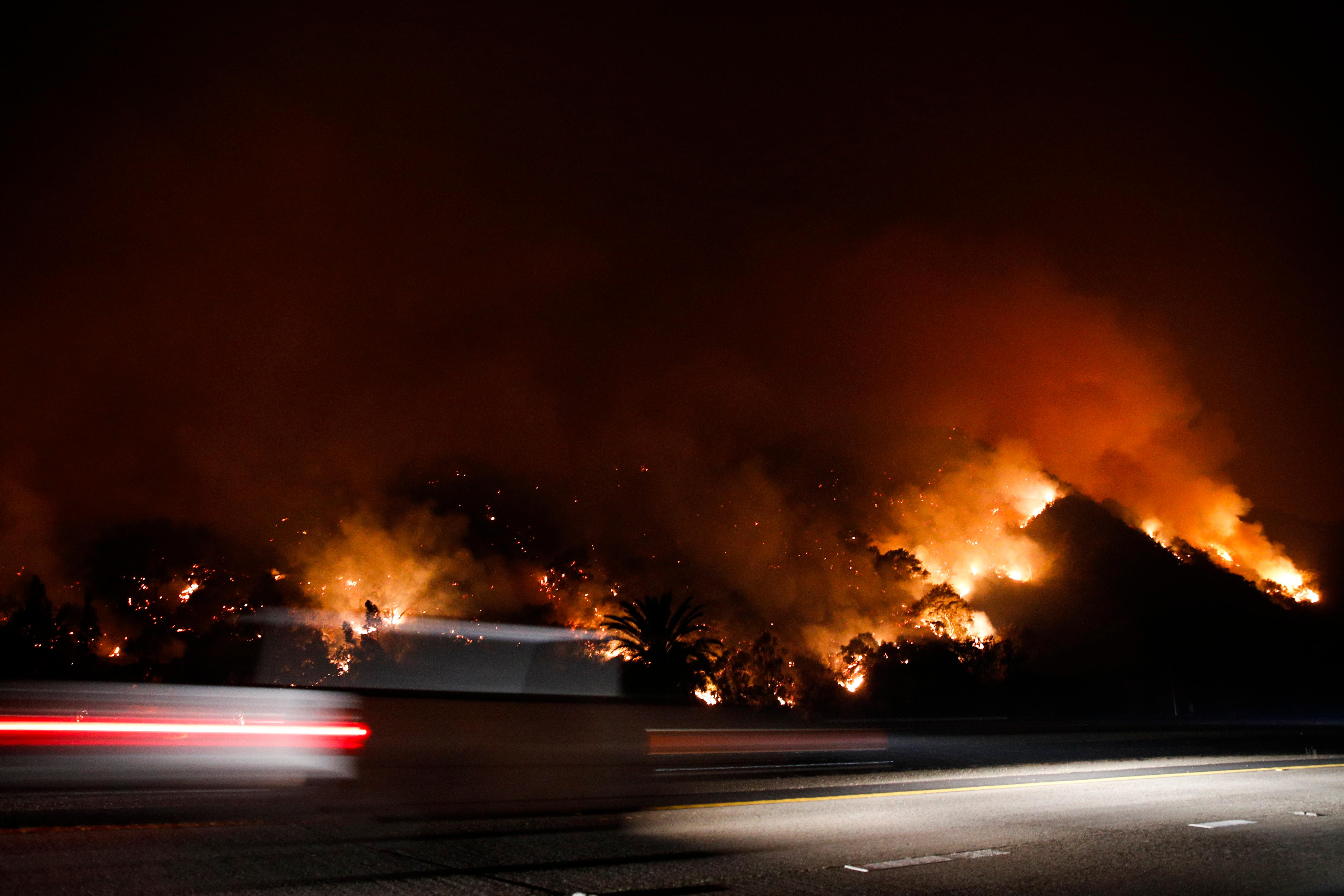 Traffic moves along the Highway 33 as a wildfires continues to burn Tuesday, Dec. 5, 2017, near Oak View, Calif. Raked by ferocious Santa Ana winds, explosive wildfires northwest of Los Angeles and in the city's foothills burned a psychiatric hospital and scores of homes and other structures Tuesday and forced the evacuation of tens of thousands of people. (AP Photo/Jae C. Hong)