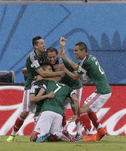 Mexico's Oribe Peralta celebrates with teammates after scoring the opening goal during the group A World Cup soccer match between Mexico and Cameroon in the Arena das Dunas in Natal, Brazil, Friday, June 13, 2014.