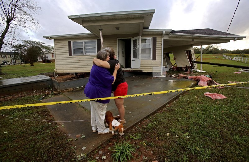 <p>JoAnn Perez, right, hugs friend Melissa Porter in front of her damaged home in Shelby, N.C., Monday, Oct. 23, 2017. Perez arrived home shortly after Monday's storms to see her home pushed away from its foundation. Her two dogs and cats were the only occupants when the storm hit. All three pets were uninjured. (Brittany Randolph/The Star via AP)</p>