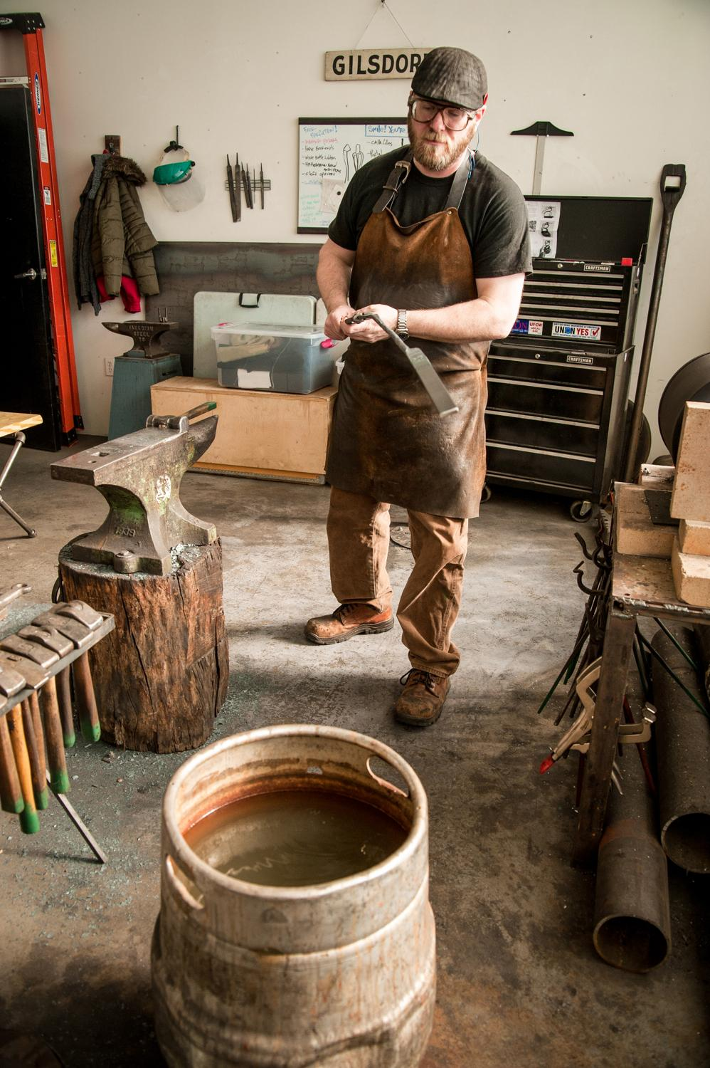 "Mark Gilsdorf dips a scalding hot piece of steel in a ""quench bucket"" to lower the temperature of the metal. He's making fireplace tongs, part of a commissioned set of tools. / Image: Melissa Doss Sliney"