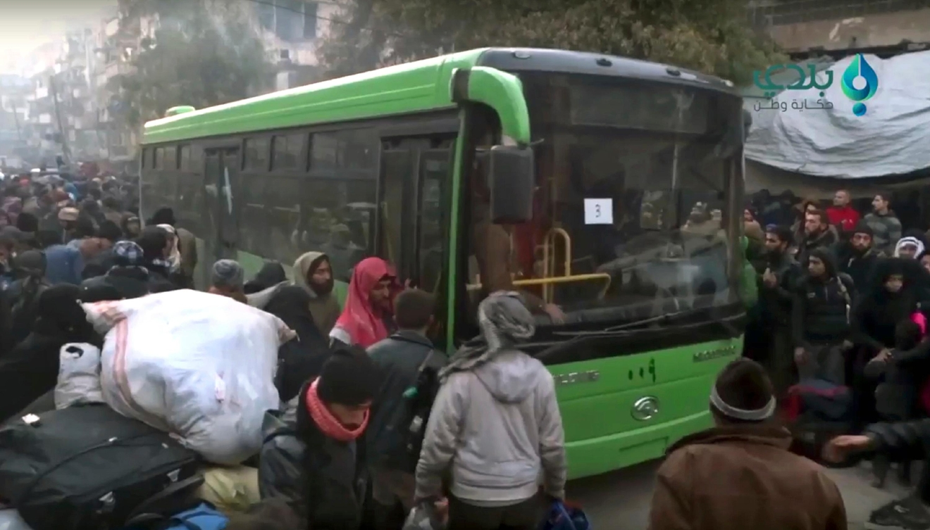 This frame grab from video provided by Baladi News Network, a Syrian opposition media outlet that is consistent with independent AP reporting, shows residents gather near a green government bus for evacuating from eastern Aleppo, Syria, Thursday, Dec. 15, 2016. The Russian military said over 1,000 people have been evacuated from Aleppo under a cease-fire deal reached with Syrian rebels. France's ambassador to the United Nations says international observers should monitor the safe evacuation of civilians and fighters from the war-torn Syrian city of Aleppo. (Baladi News Network via AP)