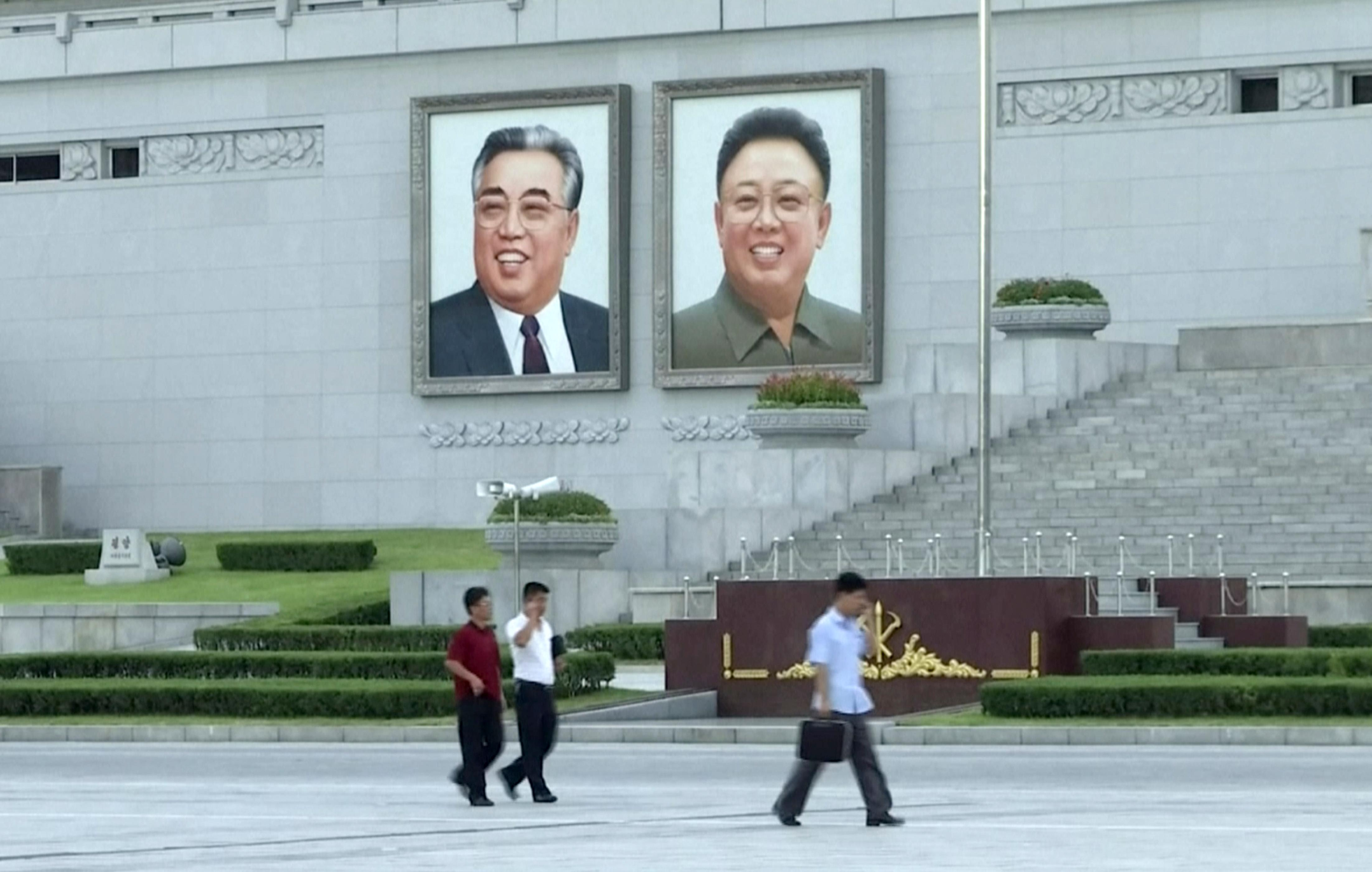 In this image made from video, pedestrians walk beneath portraits of Kim Il Sung, left, and Kim Jong Il, at Kim Il Sung square in Pyongyang, North Korea, Friday, Aug. 11, 2017. (AP Photo)