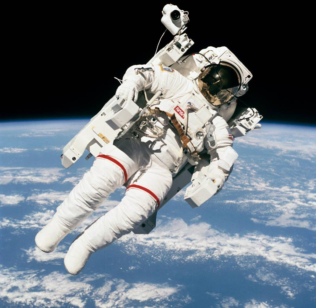 Astronaut Bruce McCandless II, STS-41-B mission specialist, uses his hands to control his movement above the Earth -- just a few meters away from the space shuttle Challenger -- during the first-ever spacewalk which didn't use restrictive tethers and umbilicals. Fellow crewmembers aboard the Challenger used a 70mm camera to expose this frame on Feb. 7, 1984, through windows on the flight deck. McCandless was joined by Robert L. Stewart, one of two other mission specialists for this flight, on two sessions of EVA. (Image Credit: NASA)