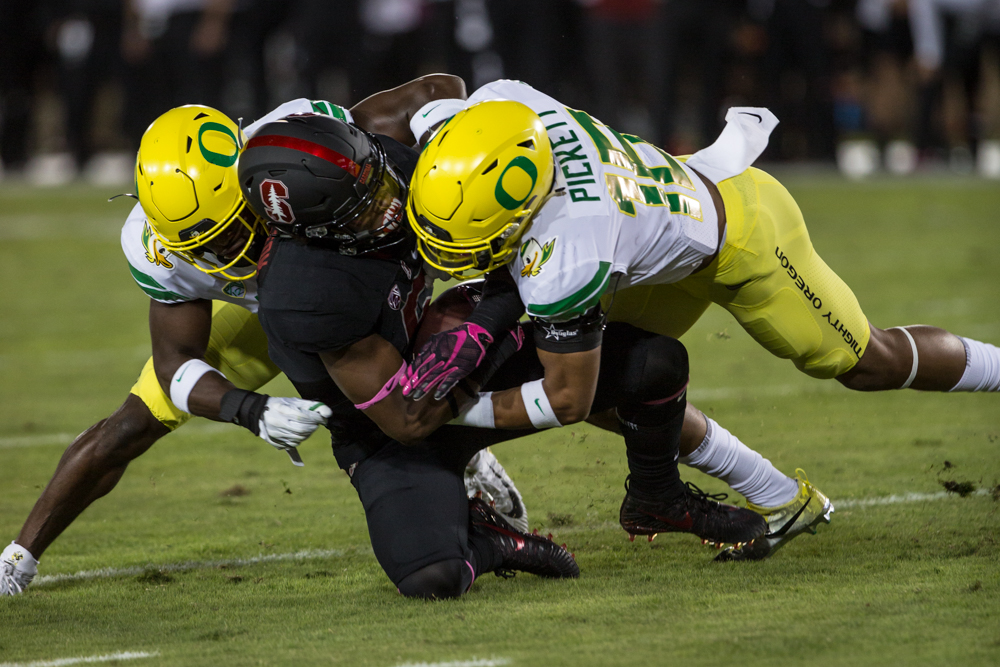 Two Oregon defenders bring down the Stanford ball carrier. The Oregon Ducks are trailing the Stanford Cardinal 28-7 at halftime at Stanford Stadium in California.  Photo by Austin Hicks, Oregon News Lab