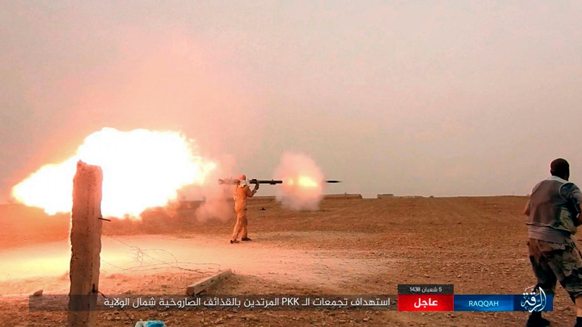 "This undated image posted online Monday, May. 1, 2017, by supporters of the Islamic State militant group on an anonymous photo sharing website, purports to show an Islamic State fighter firing his weapon during clashes with  U.S.-backed Kurdish-led Syrian Democratic Forces, in the northern Syrian province of Raqqa. The Britain-based Syrian Observatory for Human Rights and Kurdish activists said Tuesday, May 2, 2017, that a surprise attack in northeastern Syria carried out by IS has killed over 20 people, including displaced civilians. Arabic banner reads, ""Targeting gatherings of the infidel PKK with automatic weapons north of the province."" (Militant Photo via AP)"