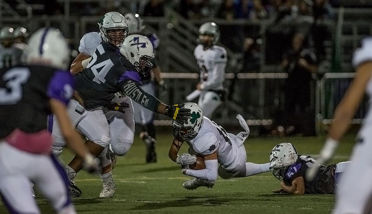 South Eugene Axemen defensive lineman Jahi Richardson (#54) reaches to stop the Sheldon Irish ball carrier from moving the ball further.                  The Sheldon Irish defeated the South Eugene Axemen 63-6 at South on Friday night. Photo by Abigail Winn, Oregon News Lab