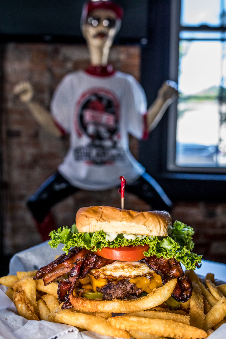 The Hangover Henry: 1/2 pound beef burger, cheddar cheese, fried egg, 2 strips of bacon, lettuce, tomato, chopped onion, pickle, and mayonnaise on a heavy duty bun / Image: Catherine Viox // Published: 9.4.20