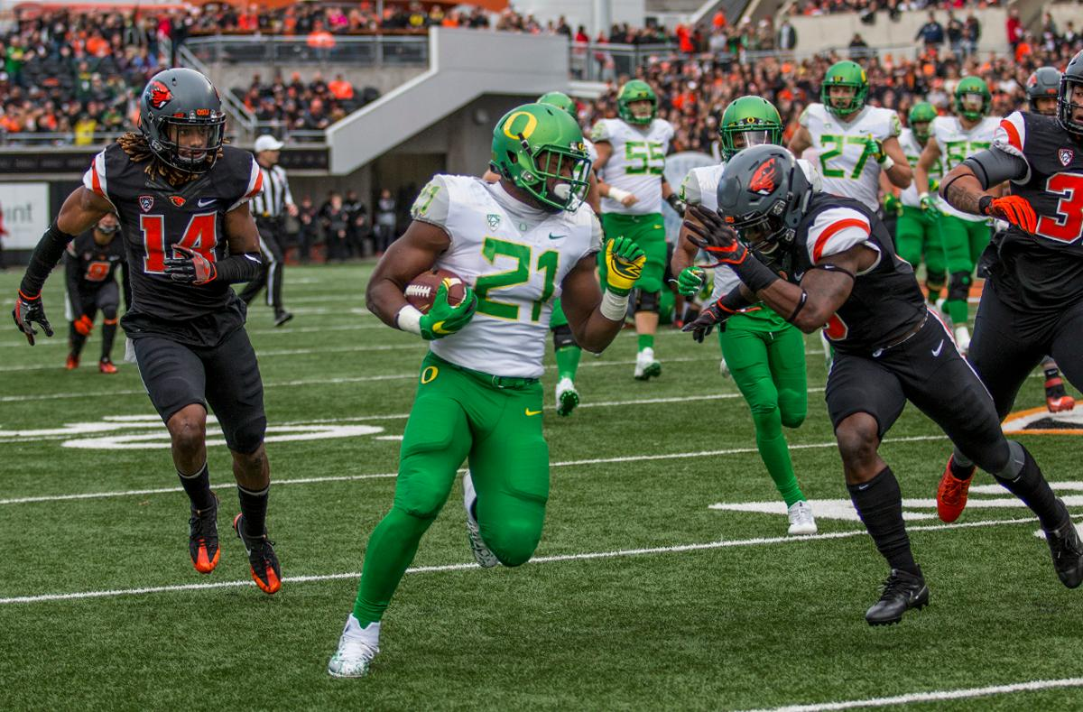 Oregon Ducks Royce Freeman (#21) rushes down field against Oregon State Beavers defense. The Oregon State University Beavers hosted the 120th Civil War against the University of Oregon Ducks on Saturday afternoon at Reser Stadium in Corvallis, Ore. The Oregon State Beavers beat the Oregon Ducks 34-24 breaking an eight-year losing streak. Photo by Katie Pietzold