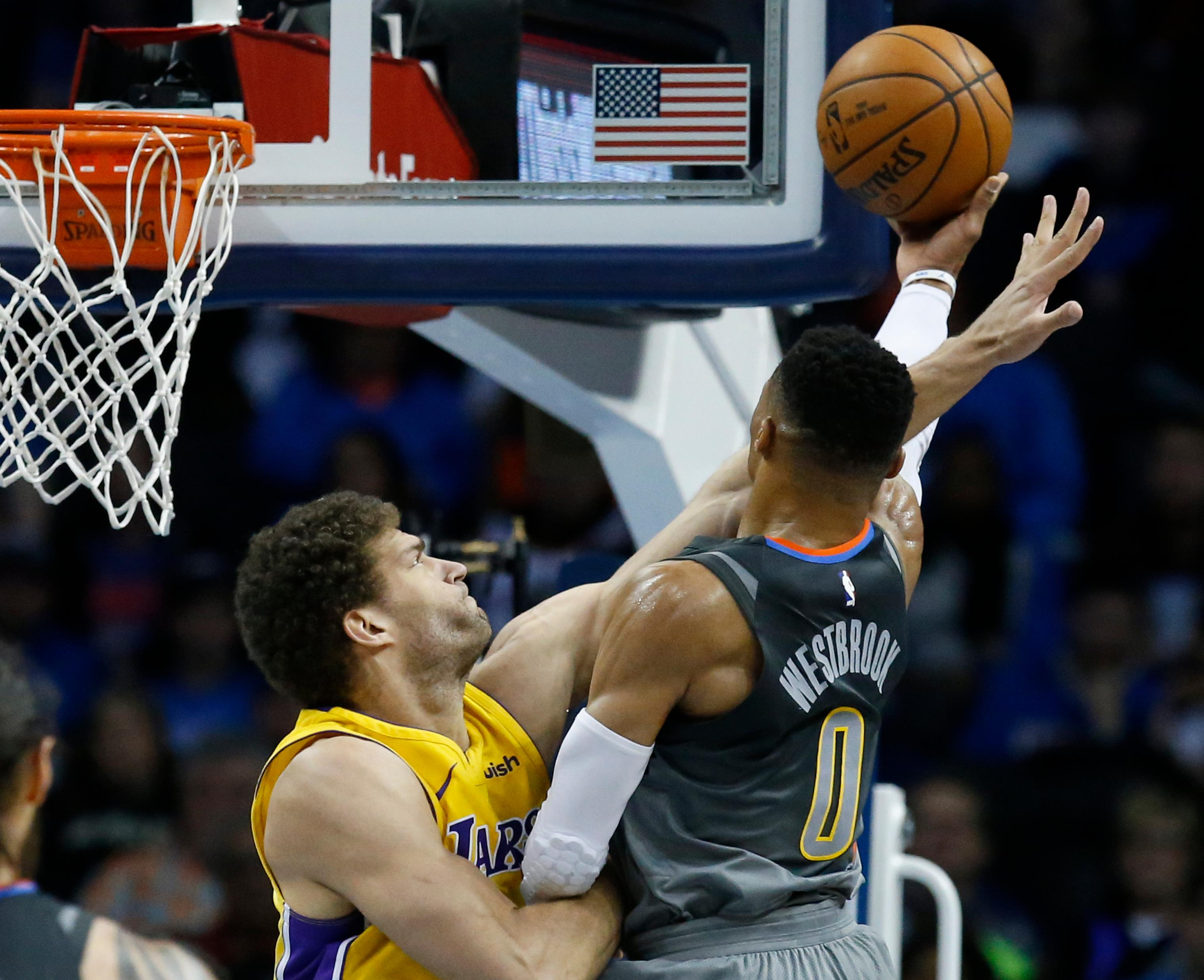 Los Angeles Lakers center Brook Lopez, left, fouls Oklahoma City Thunder guard Russell Westbrook (0) as Westbrook shoots in the first half of an NBA basketball game in Oklahoma City, Sunday, Feb. 4, 2018. (AP Photo/Sue Ogrocki)