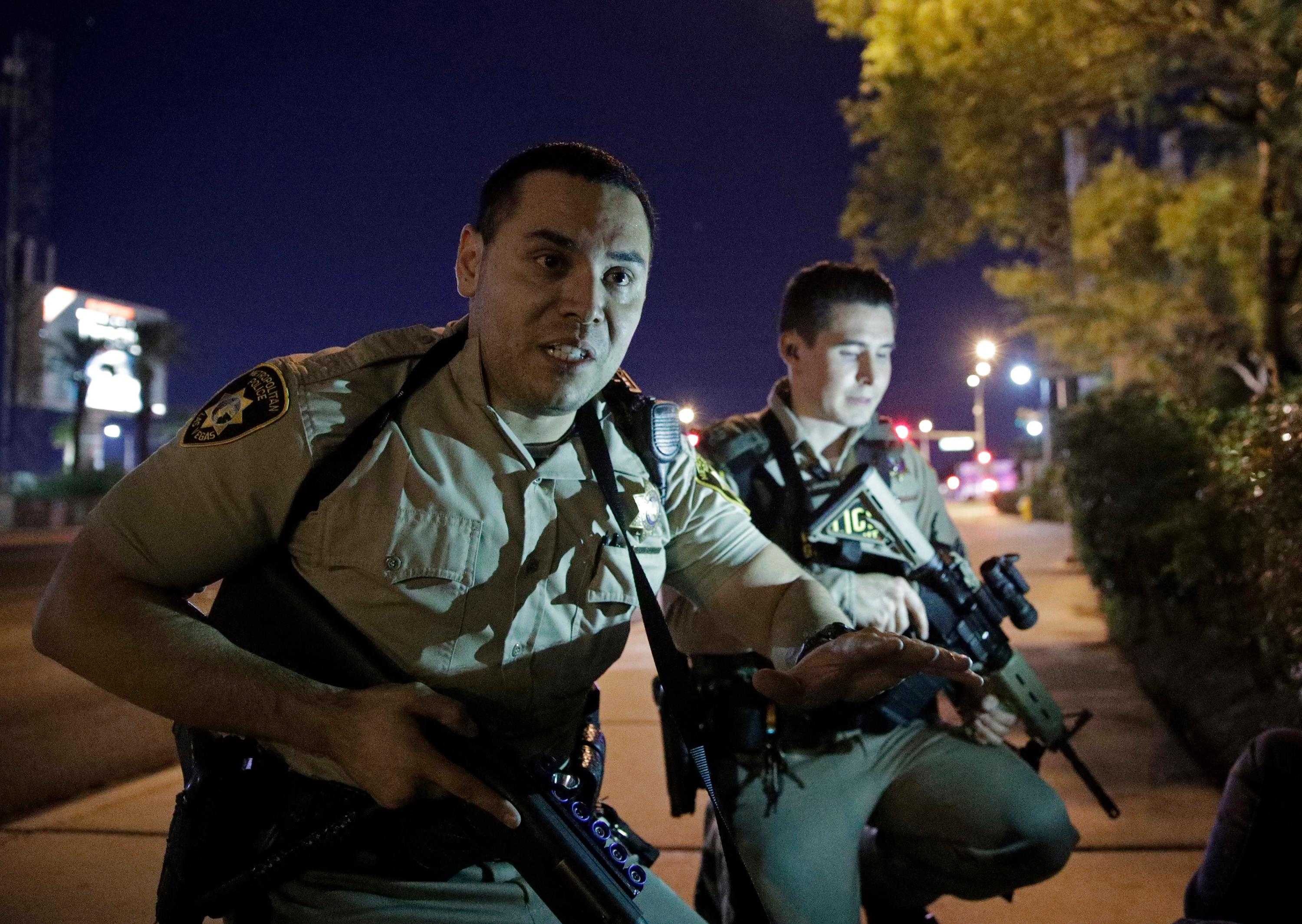 FILE - In this Sunday, Oct. 1, 2017 file photo, police officers tell people to take cover near the scene of a shooting near the Mandalay Bay resort and casino on the Las Vegas Strip, after Stephen Paddock opened fire on the Route 91 Harvest Festival killing dozens and wounding hundreds. The name of a man identified in court documents as a person of interest in the deadliest mass shooting in modern U.S. history was publicly revealed because of a court error. Clark County District Court Judge Elissa Cadish said Tuesday, Jan. 30, 2018, that her staff failed to black out the name in nearly 300 pages of documents released to news organizations including The Associated Press and Las Vegas Review-Journal.  (AP Photo/John Locher, File)