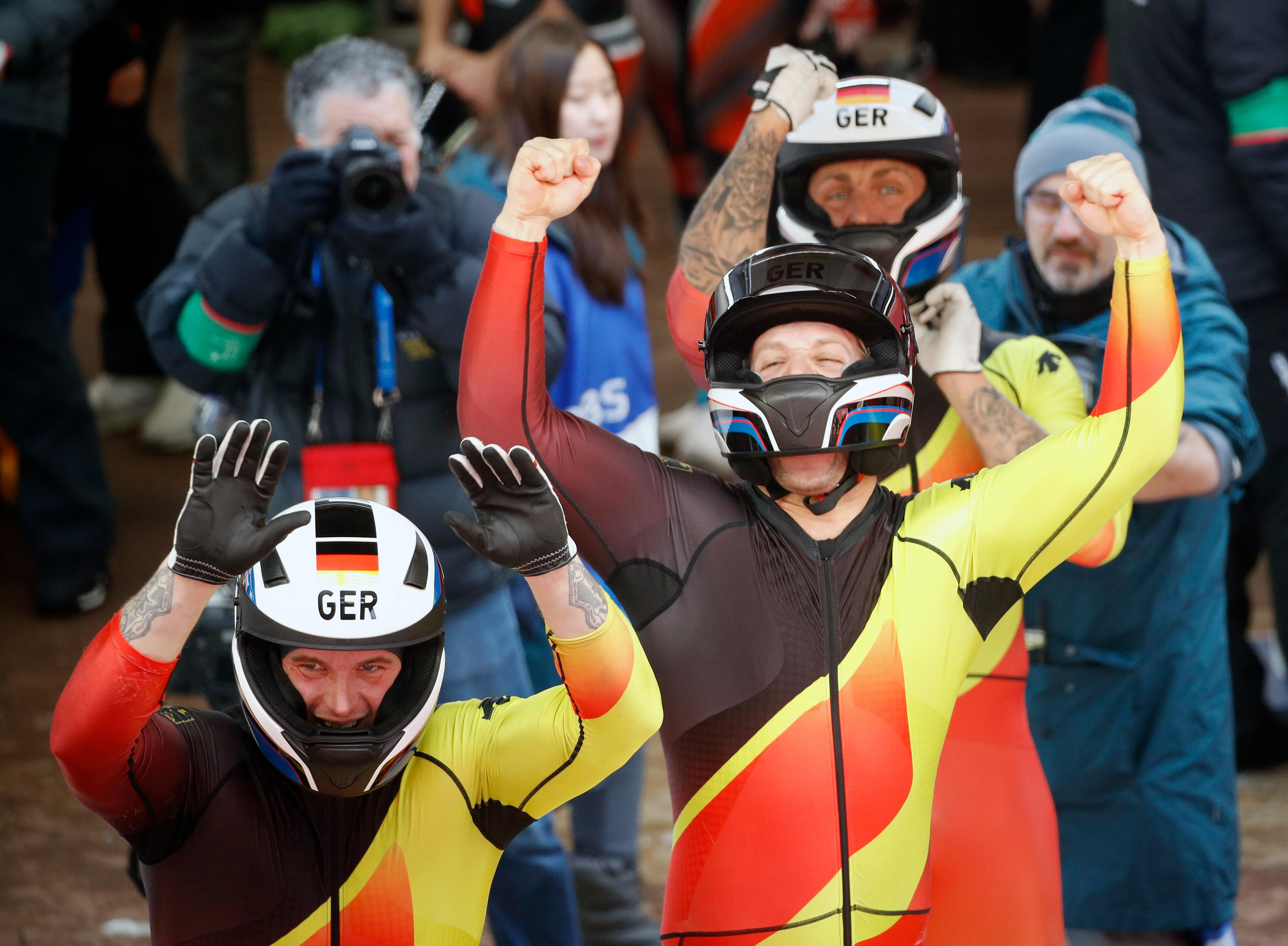 Driver Nico Walther, Kevin Kuske, Alexander Roediger and Eric Franke of Germany celebrate after tying for the silver medal during the four-man bobsled competition final at the 2018 Winter Olympics in Pyeongchang, South Korea, Sunday, Feb. 25, 2018. (AP Photo/Charlie Riedel)
