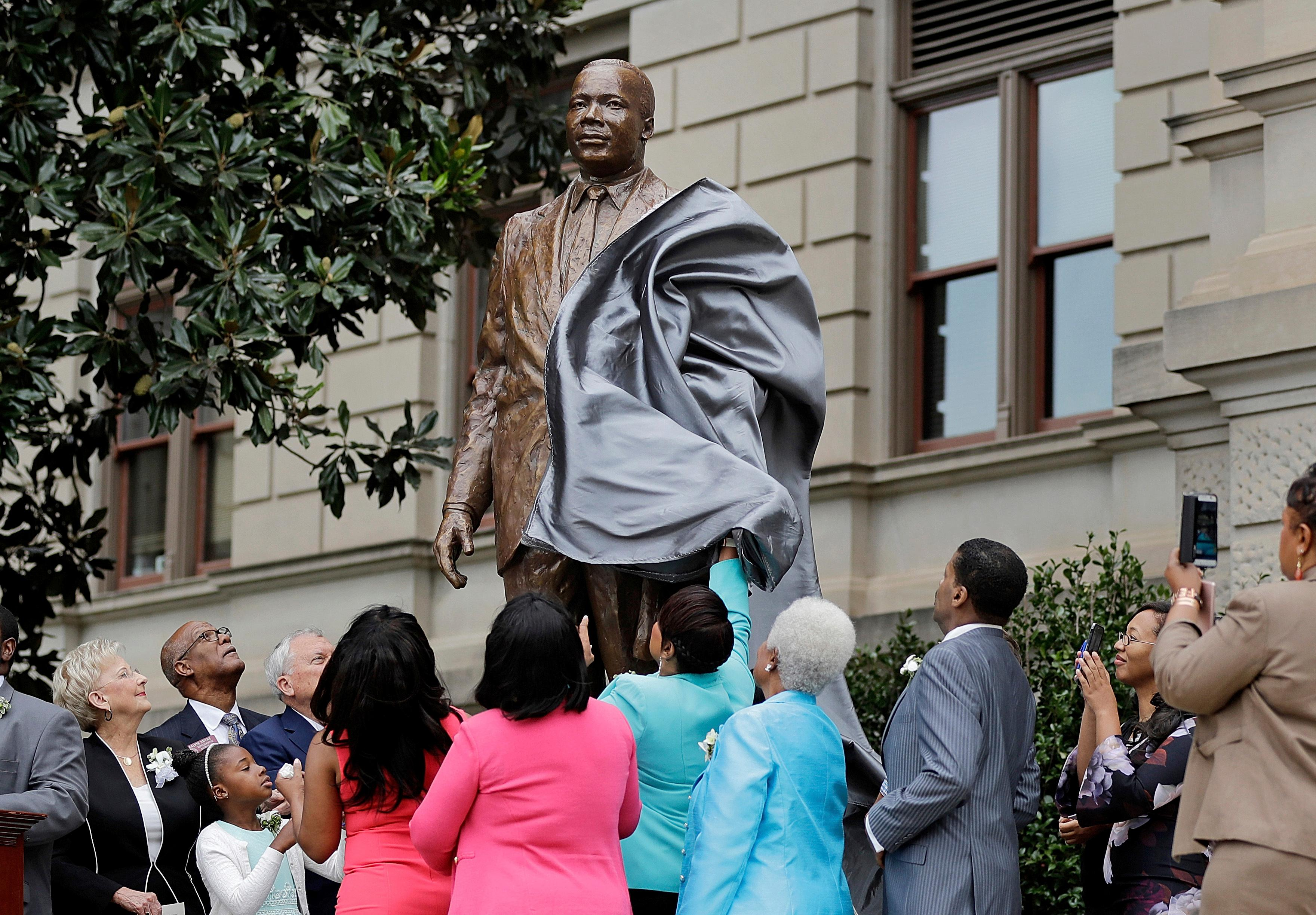 "A statue paying tribute to civil rights leader Martin Luther King Jr. is unveiled on the state Capitol grounds in Atlanta, Monday, Aug. 28, 2017. The statue's unveiling Monday came more than three years after Georgia lawmakers endorsed the project. A replica of the nation's Liberty Bell tolled three times before the 8-foot (2.44-meter) bronze statue was unveiled on the 54th anniversary of King's ""I have a dream"" speech at the march on Washington. (AP Photo/David Goldman)"