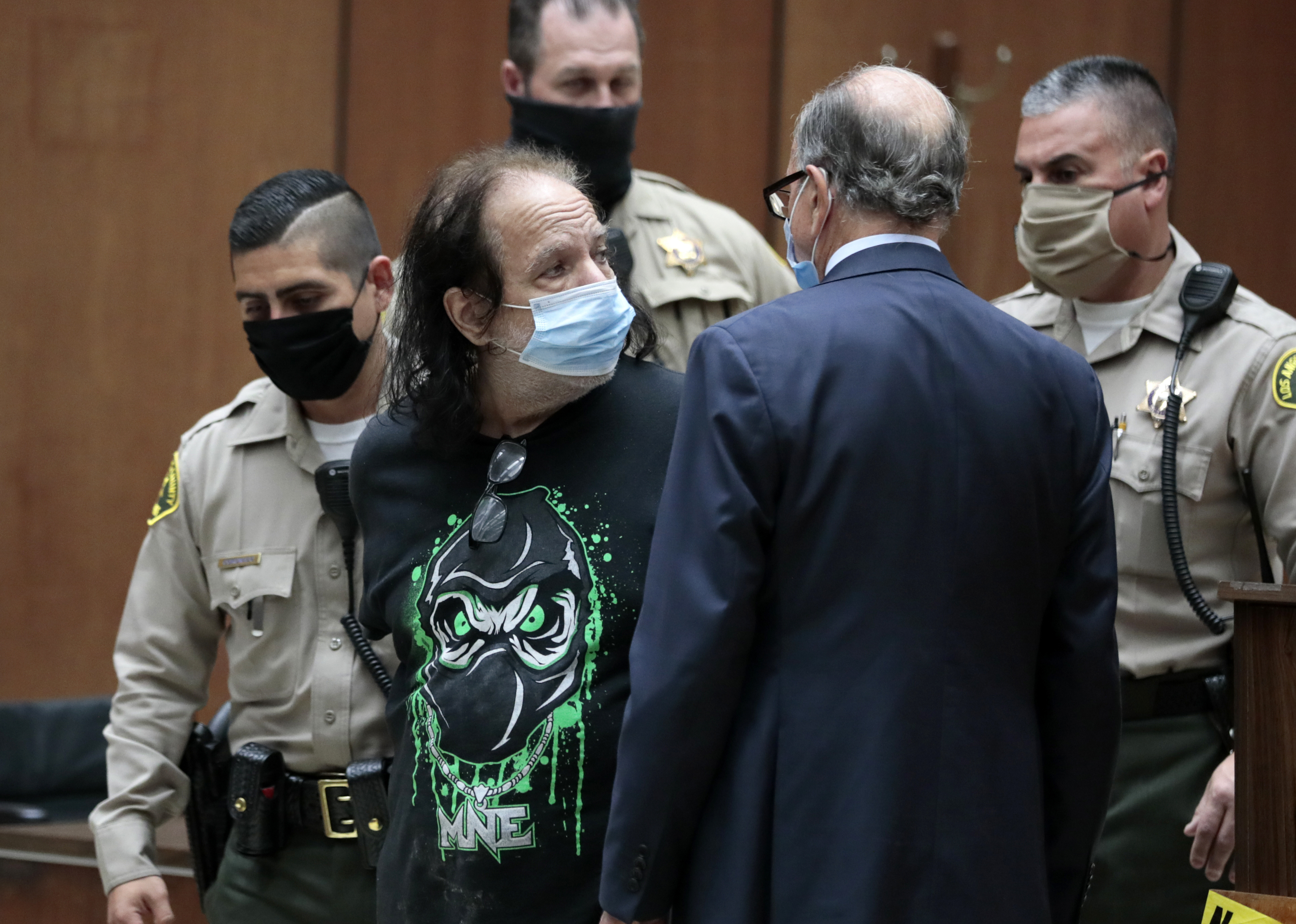 Adult film star Ron Jeremy looks over to his attorney Stuart Goldfarb, right, during an appearance at Los Angeles Superior Court in Los Angeles, Tuesday, June 23, 2020. Los Angeles County prosecutors say Jeremy has been charged with raping three women and sexually assaulting a fourth. (Robert Gauthier/Los Angeles Times via AP, Pool)