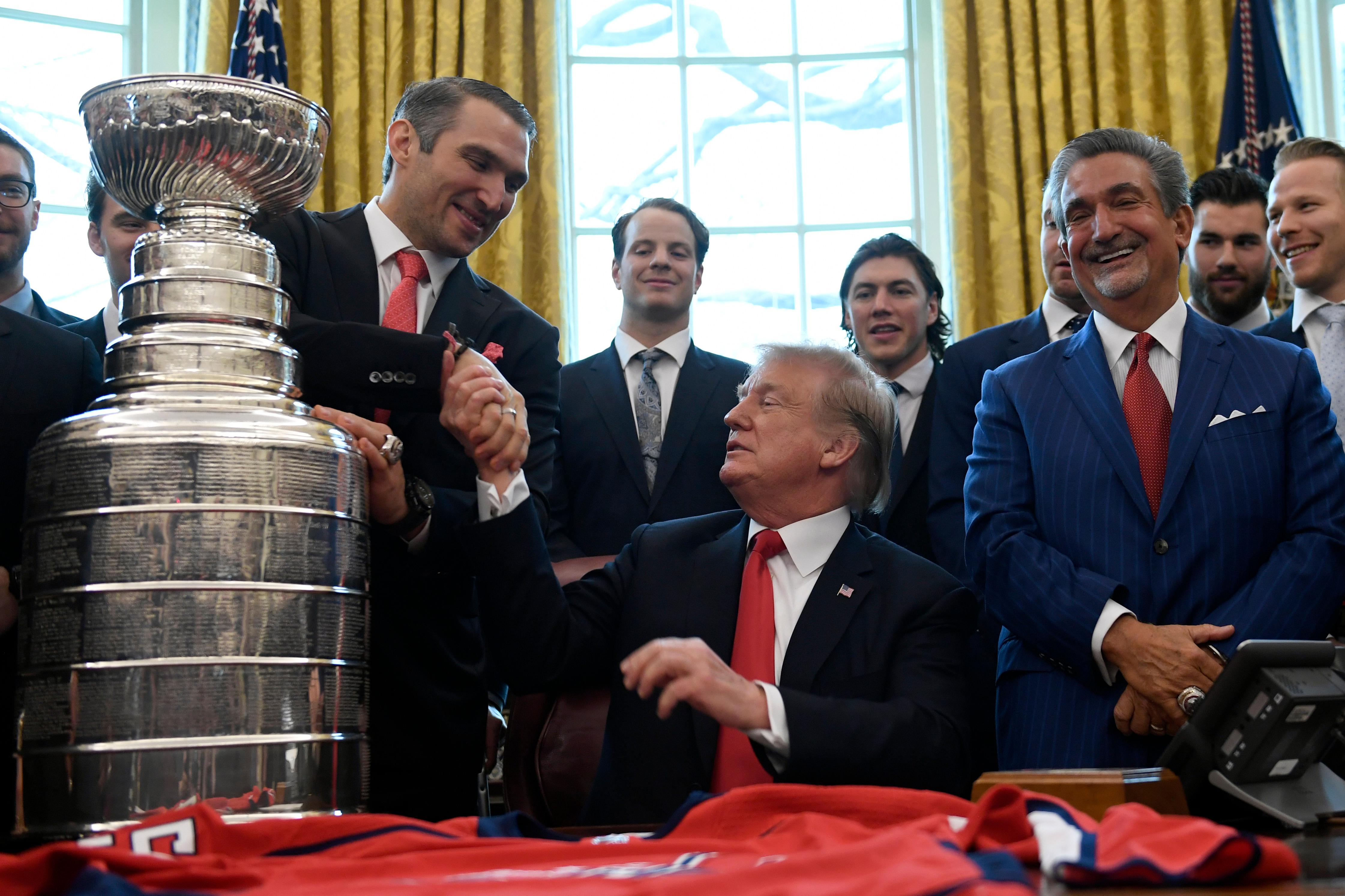 President Donald Trump, center, shakes hands with Alex Ovechkin, second from left, the captain and MVP of the 2018 Stanley Cup Champion Washington Capitals hockey team, during a visit to the Oval Office of the White House in Washington, Monday, March 25, 2019. Capitals owner Ted Leonsis, third from right, and teammates John Carlson, second from left, and T.J. Oshie, fourth from left, listen (AP Photo/Susan Walsh)