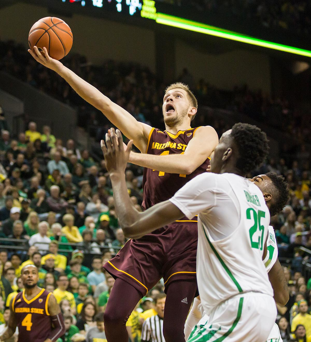 Arizona State guard Kodi Justice (#44) leaps over Oregon forward Chris Boucher (#25) for a layup. Justice ended the evening with five points and three rebounds. The Oregon Ducks defeated the Arizona State Sun Devils 71 to 70. Photo by Ben Lonergan, Oregon News Lab