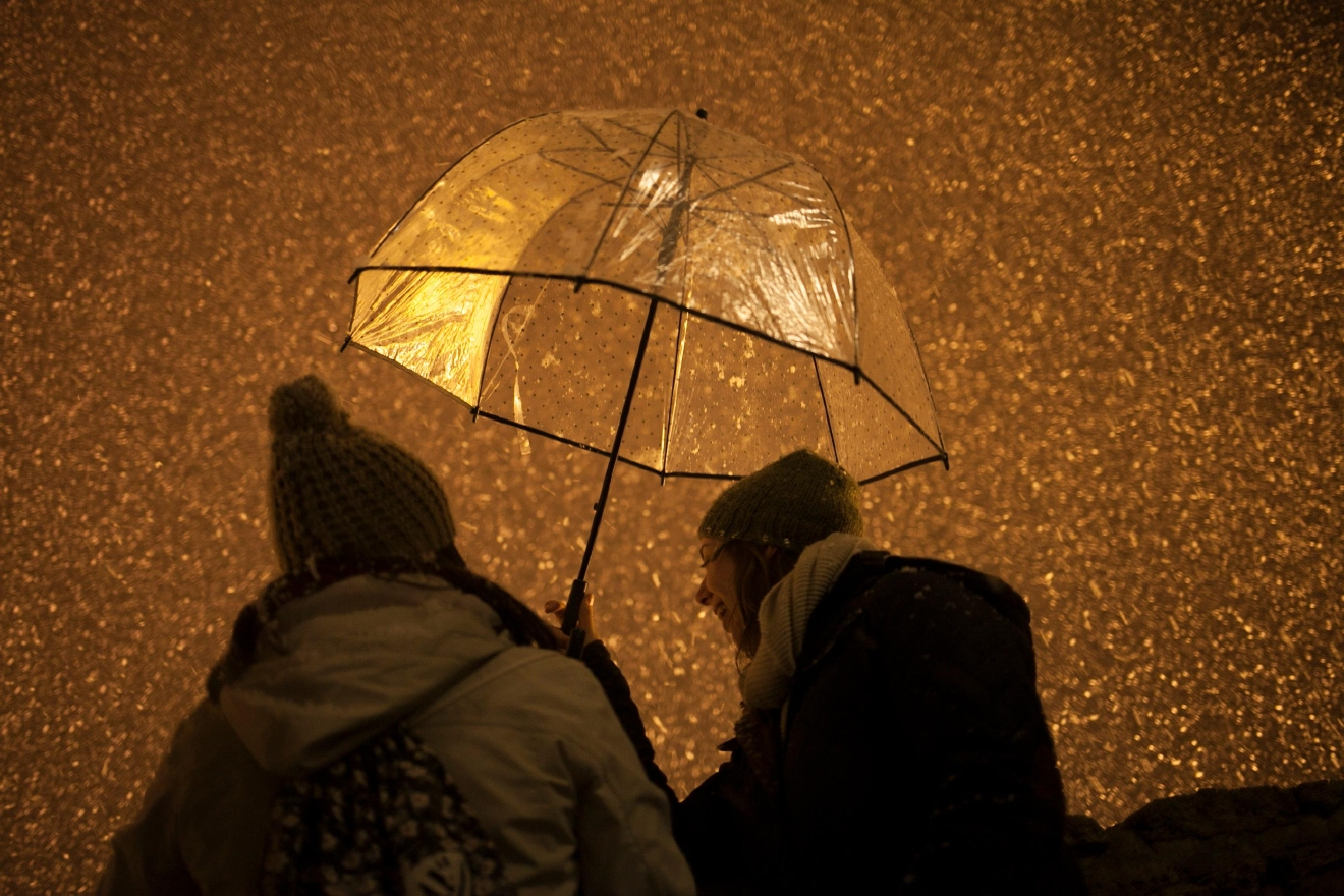 Women holding an umbrella look at snow coming down on the city of Ronda, southern Spain, Thursday, Jan. 19, 2017. (AP Photo/Javier Gonzalez)