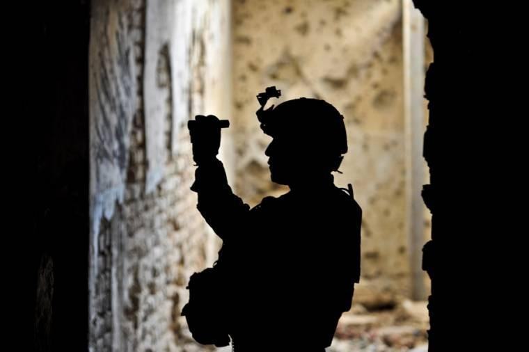 The silhouette of U.S. Army Staff Sgt. Clarence C. Elicio shows inside a tunnel at Qala-I-Jangi in northern Afghanistan's Balkh province. Elicio is using a flashlight to observe another pathway.