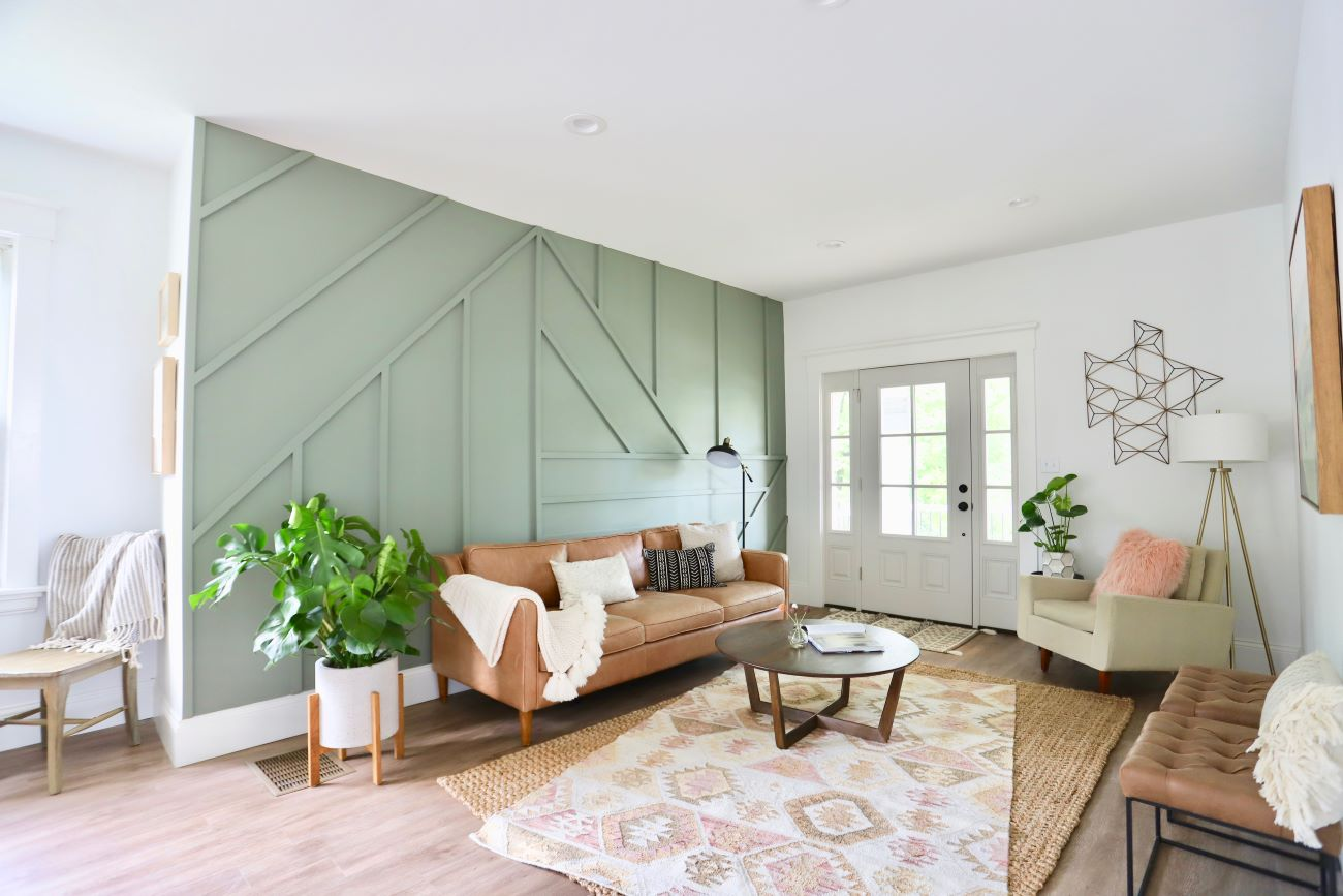 She covered over the non-working, non-original fireplace that was in desperate condition with a bold accent wall made from simple 1x2s and a neutral paint to give the large wall a focal point. By moving the front door to the other side of the room and adding a feature wall where the fireplace was, she opened the flow of the room and made it feel much bigger. / Image courtesy of Nicole Nichols // Published: 6.2.20