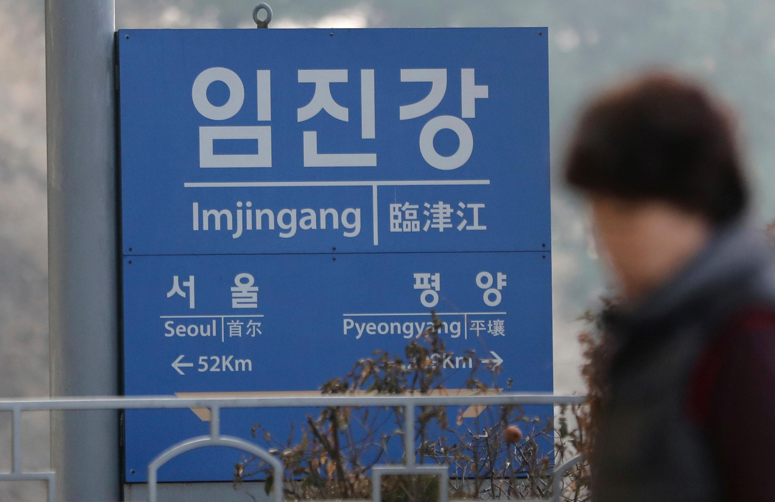 A woman walks by a signboard showing the distance to North Korea's capital Pyongyang and to South Korea's capital Seoul from Imjingang Station in Paju, South Korea, Wednesday, Jan. 17, 2018. The two Koreas are meeting Wednesday for the third time in about 10 days to continue their discussions on Olympics cooperation, days ahead of talks with the IOC on North Korean participation in the upcoming Winter Games in the South. (AP Photo/Lee Jin-man)