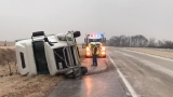 Semi overturns on ice-covered road, spills plastic crates