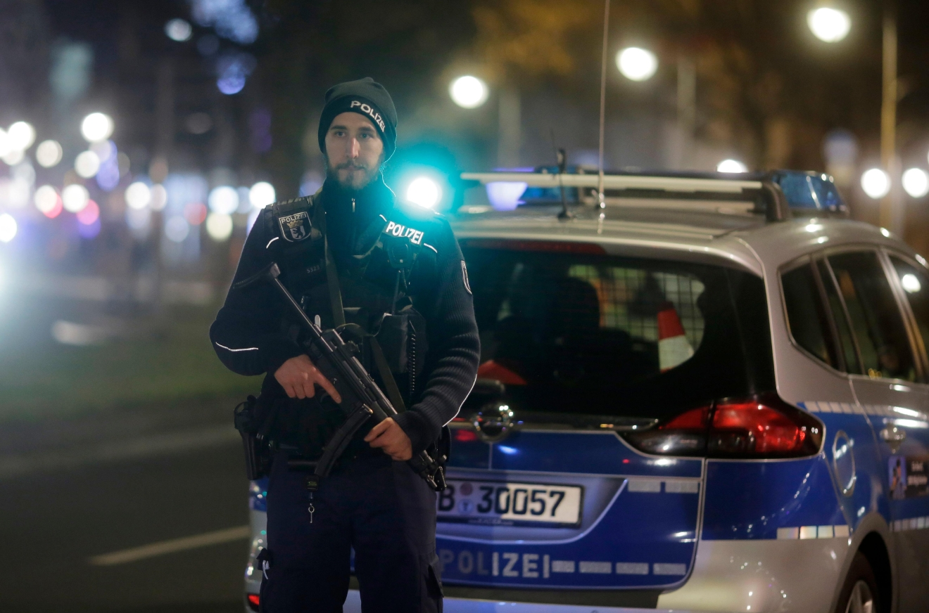A police officer with a submachine gun stands guard after a truck ran into a crowded Christmas market in Berlin, Germany, Monday, Dec. 19, 2016. Several people have been killed in the incident. (AP Photo/Markus Schreiber)