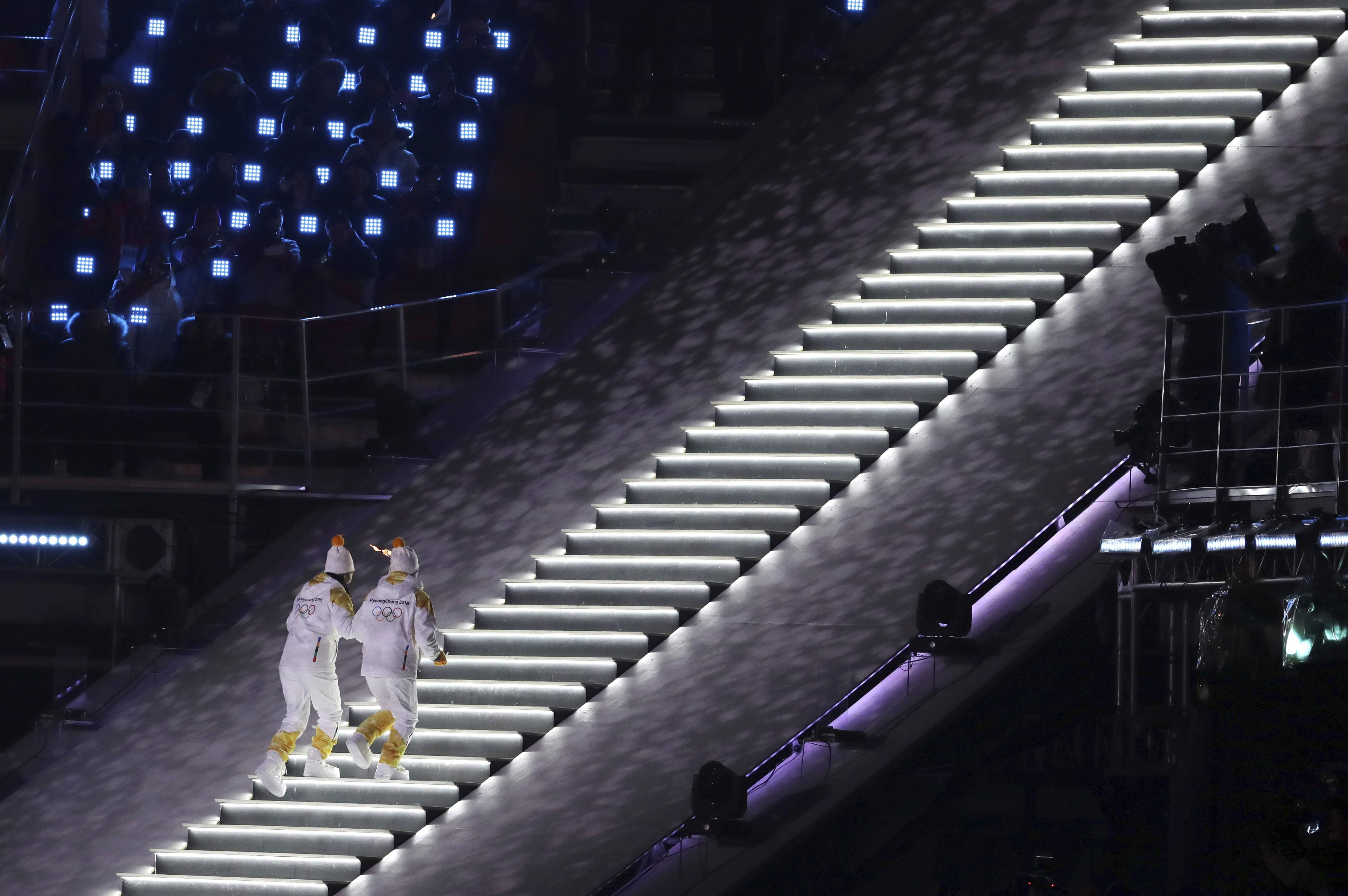 North Korea's Jong Su Hyon, left, and South Korea's Park Jong-ah carry the Olympic torch during the opening ceremony of the 2018 Winter Olympics in Pyeongchang, South Korea, Friday, Feb. 9, 2018. (AP Photo/Michael Sohn)