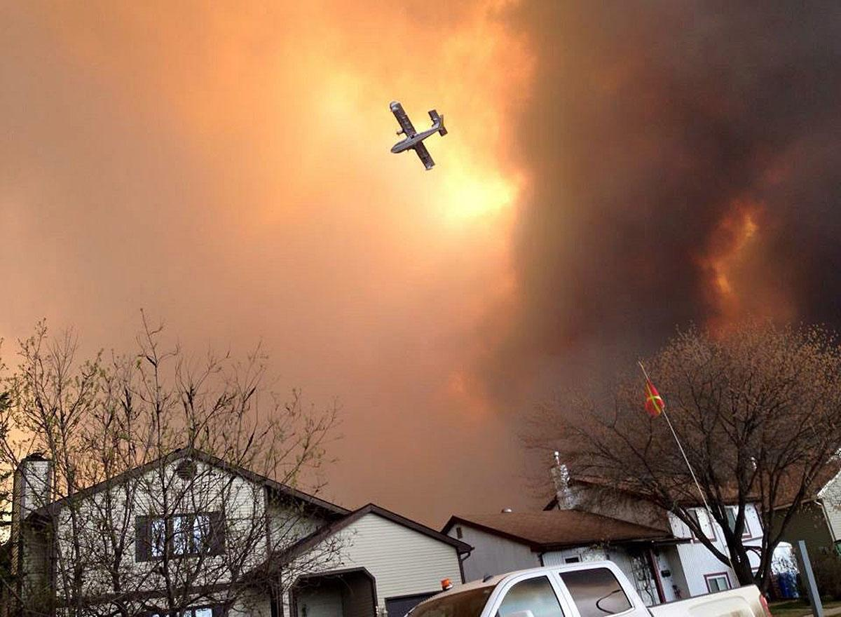 Smoke fills the air as a small plane flies overhead in Fort McMurray, Alberta, Tuesday, May 3, 2016. The entire population of the Canadian oil sands city of Fort McMurray, has been ordered to evacuate as a wildfire whipped by winds engulfed homes and sent ash raining down on residents. (Kitty Cochrane/The Canadian Press via AP) MANDATORY CREDIT