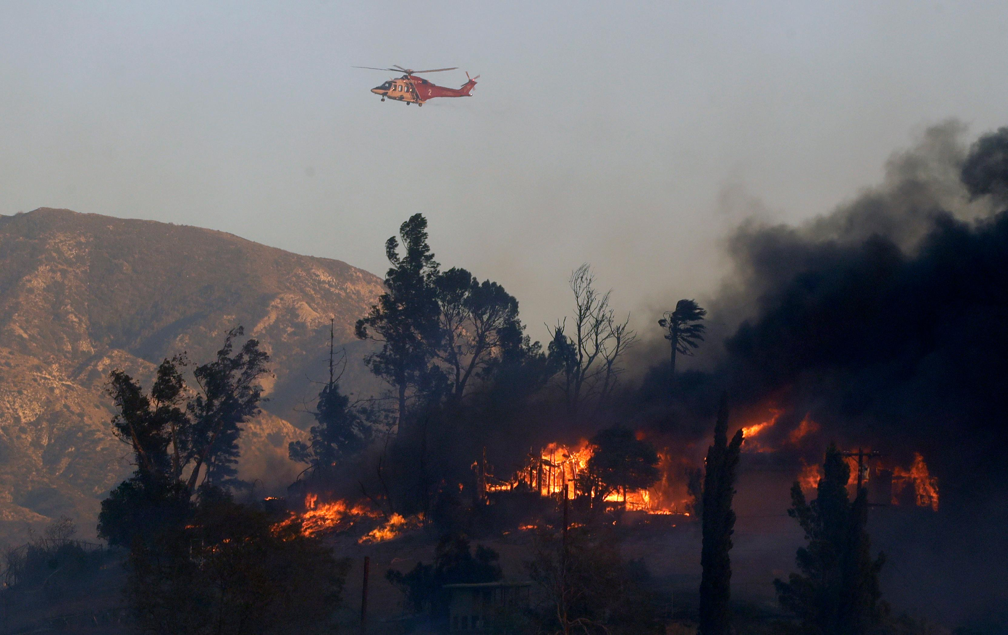 A water dropping helicopter flies over a hot spot on the Creek Fire in the Lake View Terrace area of Los Angeles, Tuesday, Dec. 5, 2017. (AP Photo/Chris Carlson)