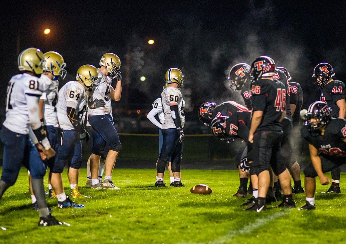 Marist Spartans and Thurston Colts gather at the scrimmage line as the heat rises off of them and into the brisk autumn night. Thurston Colts defeated Marist Catholic Spartans 50-14 to seal second place in their conference on Friday night at Thurston High School. Photo by Rhianna Gelhart, Oregon News Lab
