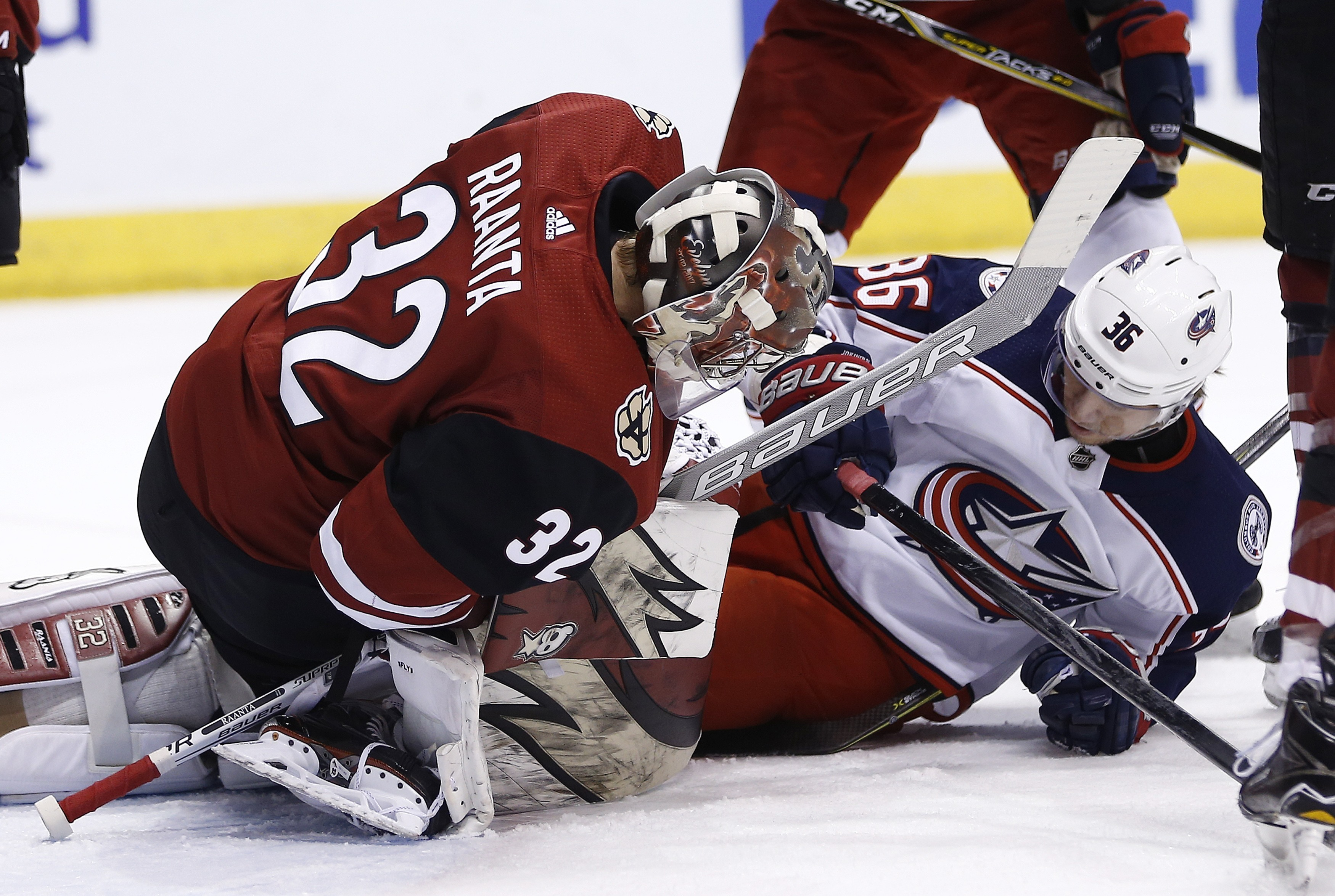 Arizona Coyotes goaltender Antti Raanta (32) makes a save as he collides with Columbus Blue Jackets left wing Jussi Jokinen (36) during the first period of an NHL hockey game, Thursday, Jan. 25, 2018, in Glendale, Ariz. (AP Photo/Ross D. Franklin)