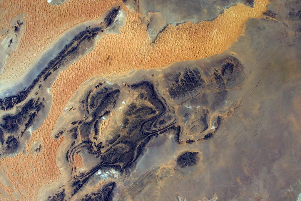 The battle sand vs. rock is a constant in the desert, and makes for fantastic abstract shapes, seen from space (Photo & Caption: Thomas Pesquet // NASA)