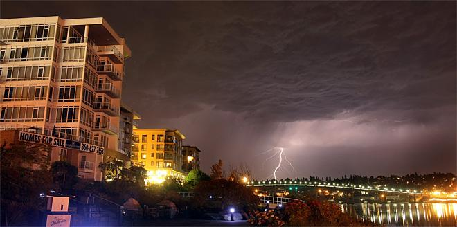A bold of lightning hits above the Manette Bridge from downtown Bremerton, Wash., near the Harborside Condominiums early Monday, July 9, 2012. (AP Photo/Kitsap Sun, Larry Steagall)