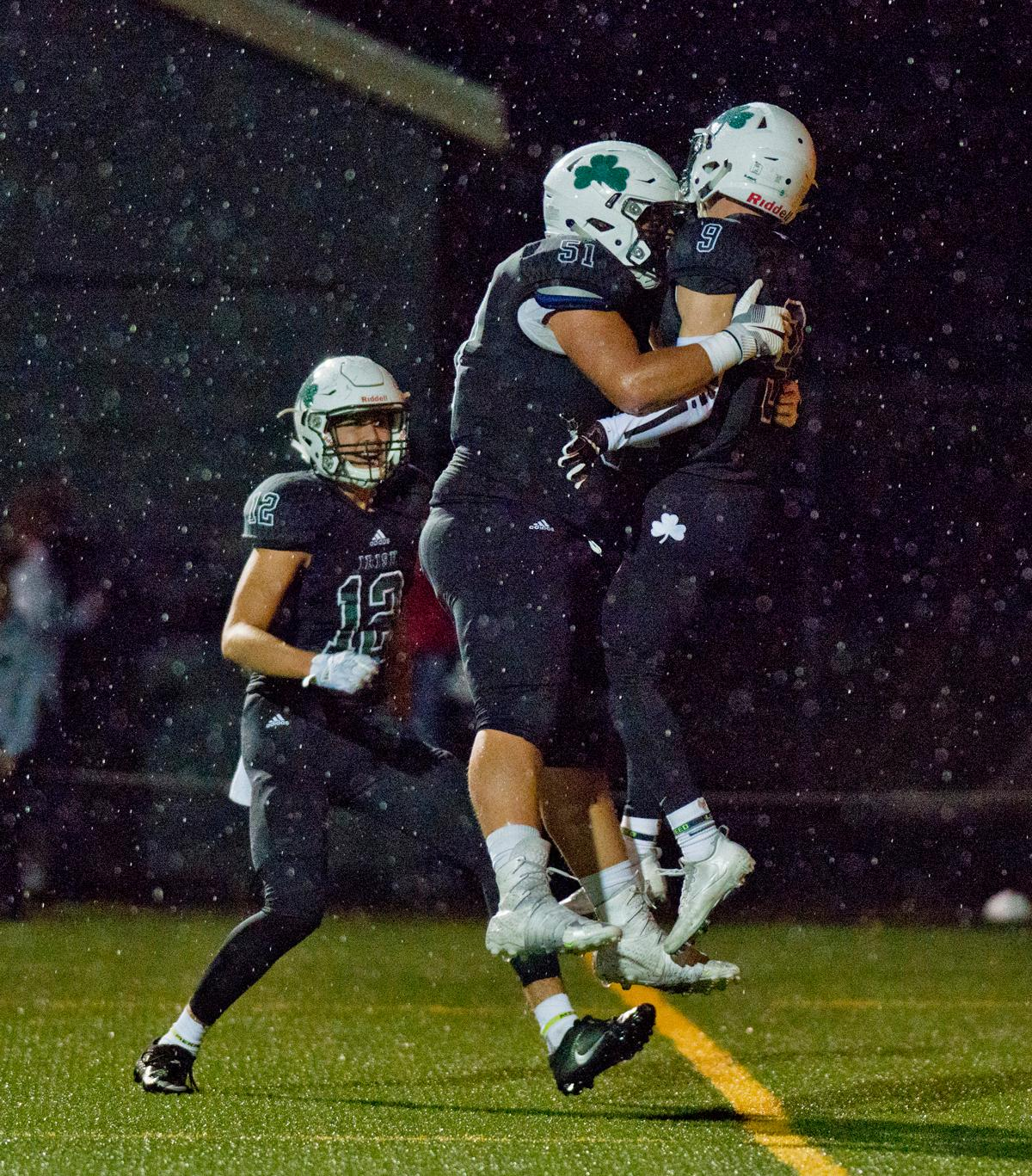 Sheldon Irish wide receiver Uta Mageo (#12), offensive lineman Austin Lasby (#51) and wide receiver Jack Folsom (#9) celebrate in the end zone after Folsom scored a touchdown. On a rainy Monday evening Sheldon defeated West Salem 41-7. The game had been postponed from Friday due to unhealthy levels of smoke in the atmosphere due to nearby forest fires. Photo by Dan Morrison, Oregon News Lab