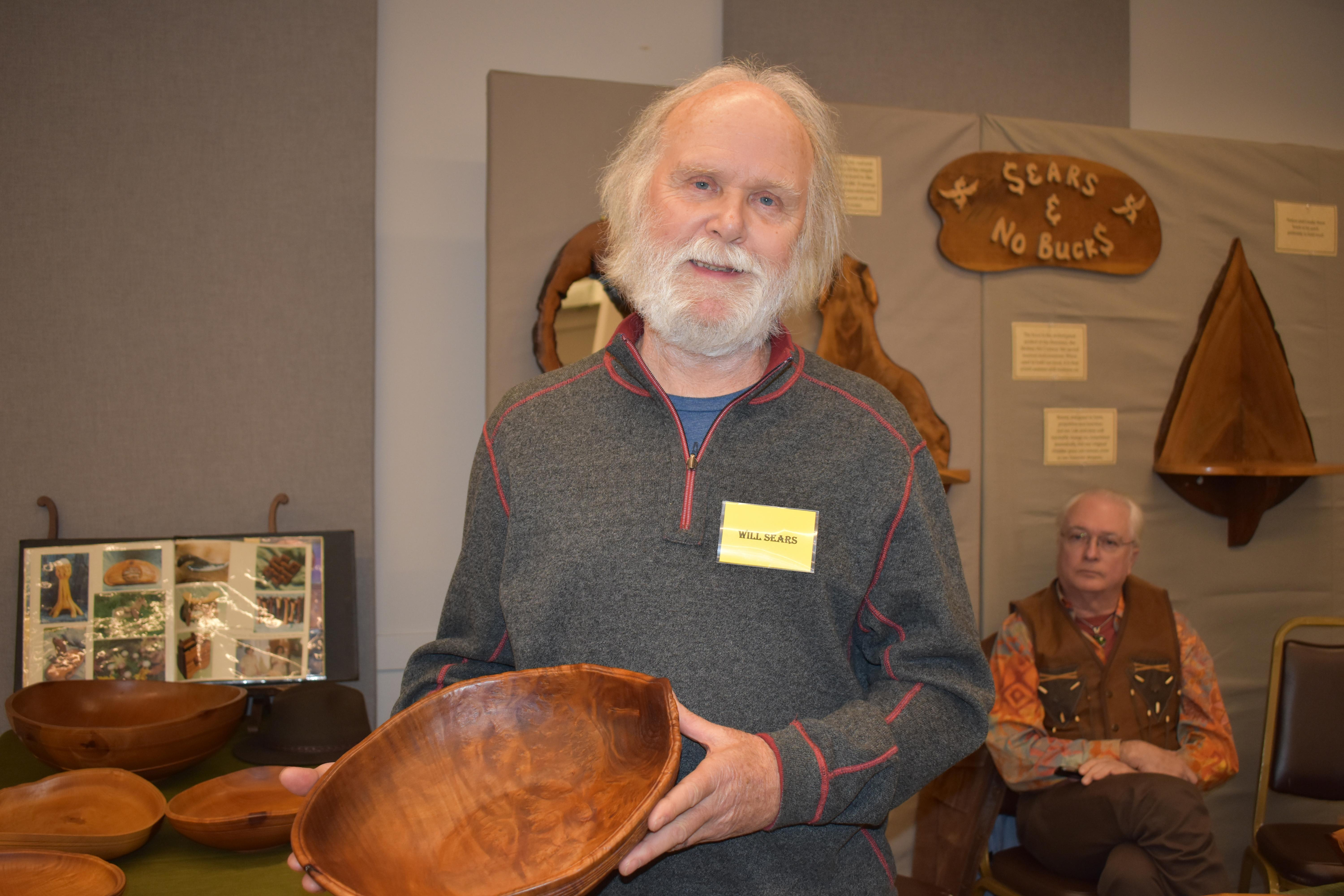 Will Sears holds one of his madrone bowls, its once perfect circle now uniquely reshaped as the wood dries and warps. Ray Barry is in the background.  Photo by Maureen Flanagan Battistella