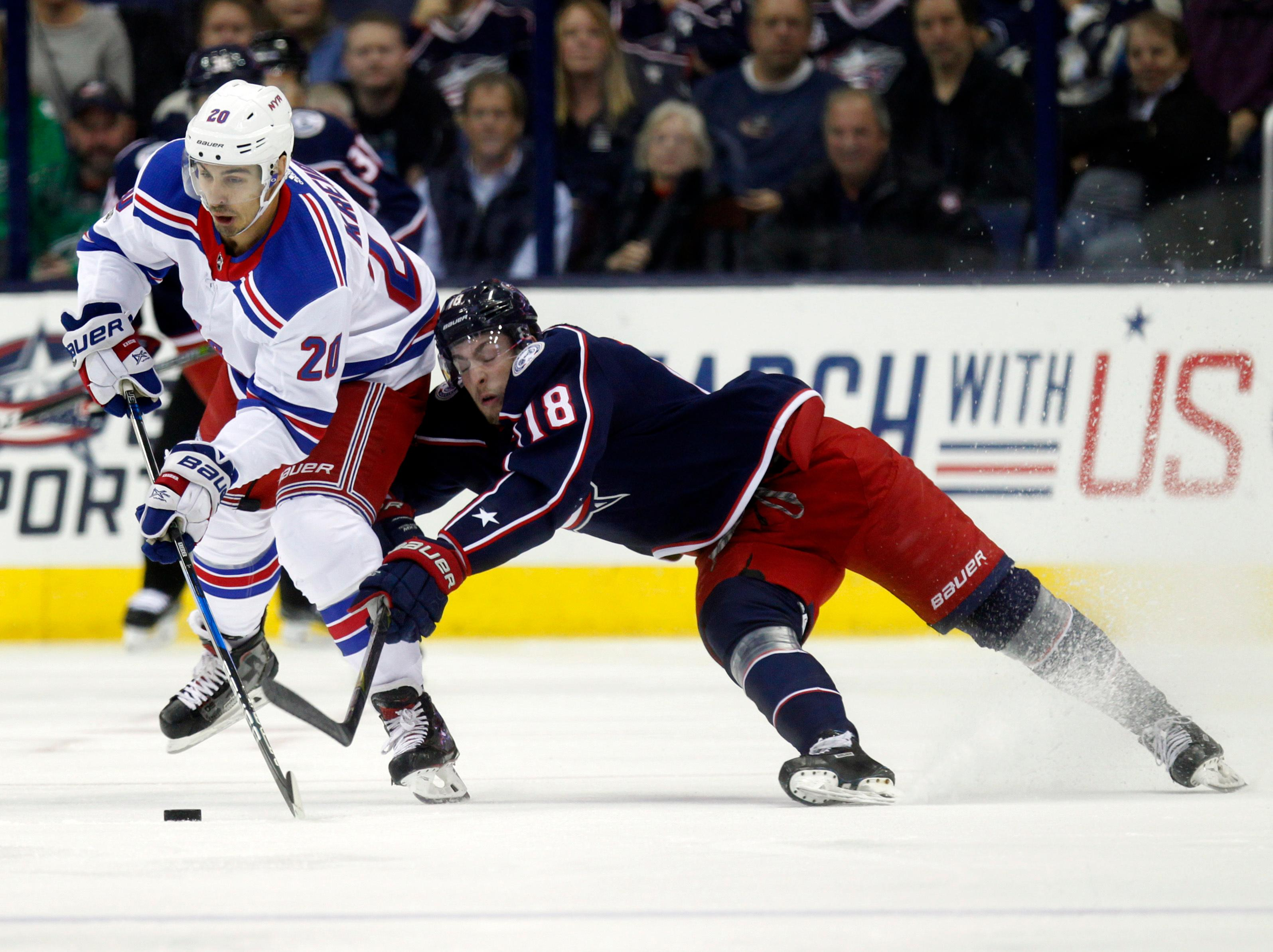 New York Rangers forward Chris Kreider, left, controls the puck against Columbus Blue Jackets forward Pierre-Luc Dubois during the first period of an NHL hockey game in Columbus, Ohio, Friday, Oct. 13, 2017. (AP Photo/Paul Vernon)