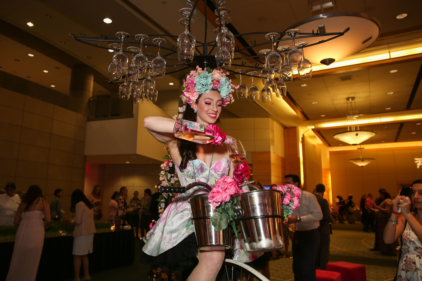 Hundreds of people celebrated the start of cherry blossom season with the annual Pink Tie Party at the Ronald Reagan Building on March 22. Guests clad in pink were treated to bites from local restaurants, live music, artistic performances and a visit from a woman on a large tricycle pouring rosé.{ } (Amanda Andrade-Rhoades/DC Refined)