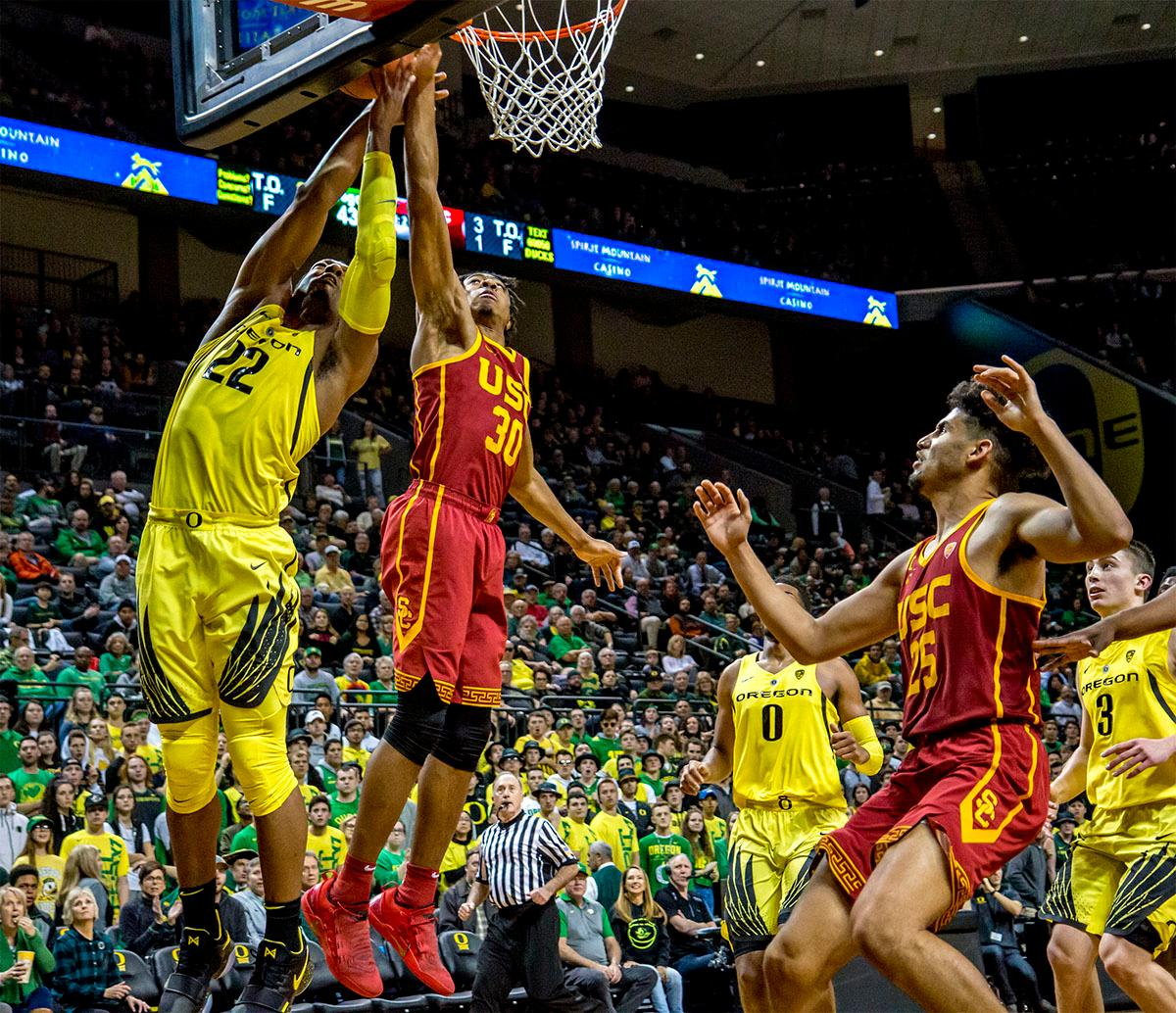 The Duck's MiKyle McIntosh (#22) and the Trojan's Elijah Stewart (#30) compete for the rebound. The UO Ducks basketball team suffered a loss to the USC Trojans, 75-70, at Matthew Knight Arena on Thursday. Payton Pritchard lead the scoring with 18 points. The Ducks are now 2-4 in conference play and 12-7 overall. The Ducks will next play the UCLA at Matthew Knight Arena at 7:15 p.m. on Saturday, Jan. 20. Photo by August Frank, Oregon News Lab