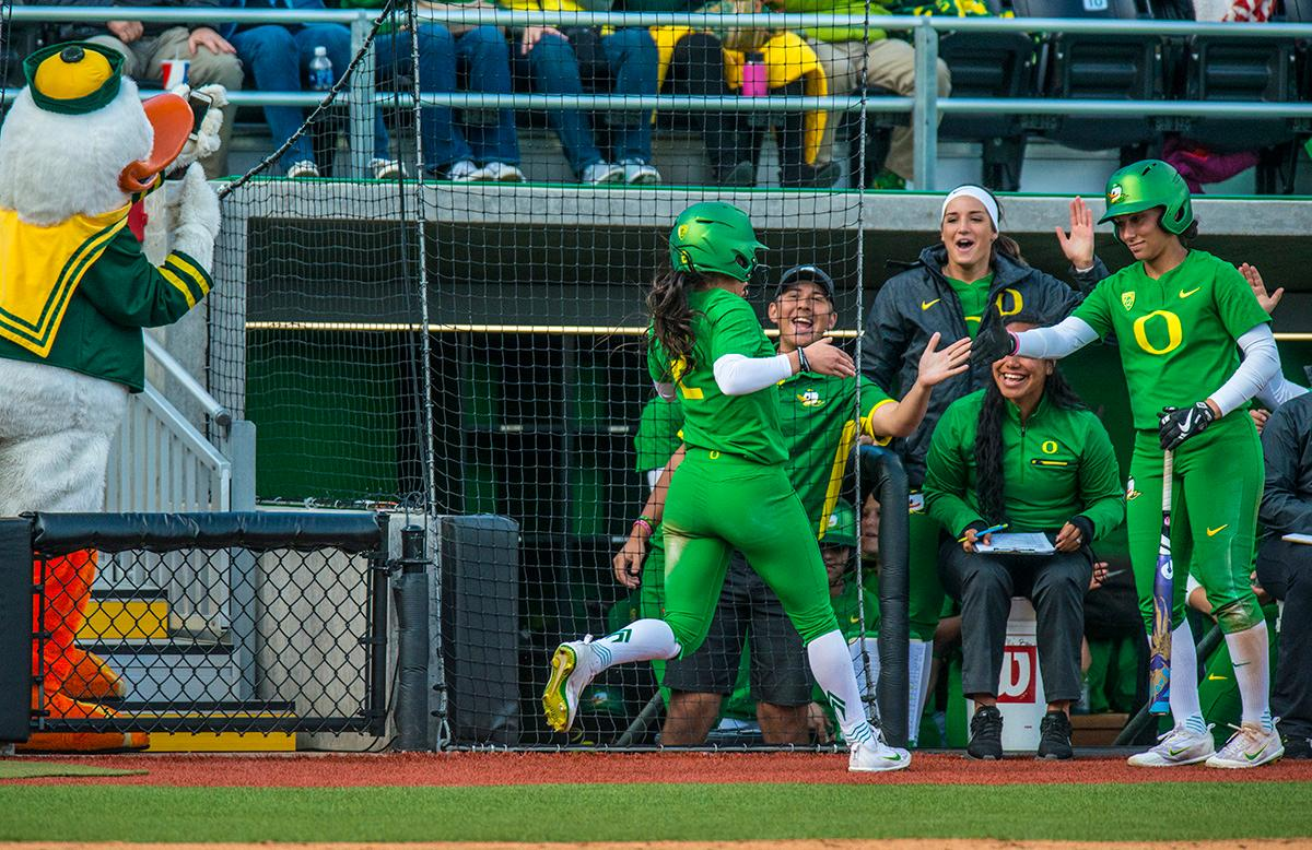 The Oregon Ducks team congratulates right fielder Danica Mercado (#2) after she makes it home for a run. The No. 5 Oregon Ducks defeated the No. 2 Florida State Seminoles in both games of the doubleheader (11-0, 3-1) on Saturday afternoon. This sweep of the first two rounds of the postseason happened in front of a soldout crowd of 2,517 at Jane Sanders Stadium. Photo by Rhianna Gelhart, Oregon News Lab