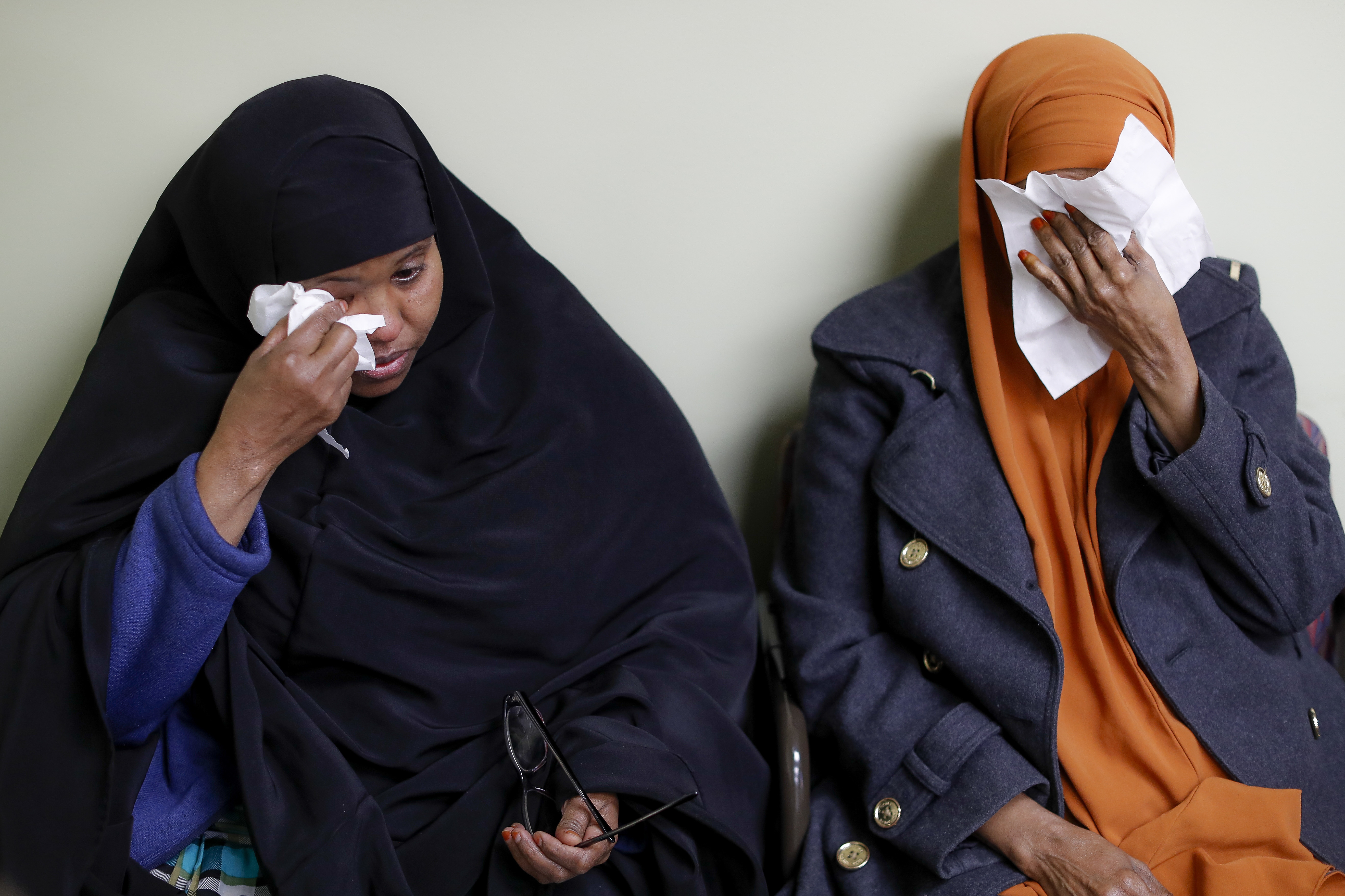 FILE - In this March 16, 2017, file photo, Somali refugees Layla Muali, left, and Hawo Jamile, right, wipe away tears during an interview at the Community Refugee & Immigration Services offices in Columbus, Ohio. Columbus has the country's largest percentage of Somali refugees. A federal judge in Hawaii further weakened the already-diluted travel ban in a ruling Thursday, July 13, 2017, by vastly expanding the list of U.S. family relationships that visitors from six Muslim-majority countries can use to get into the country. (AP Photo/John Minchillo, File)