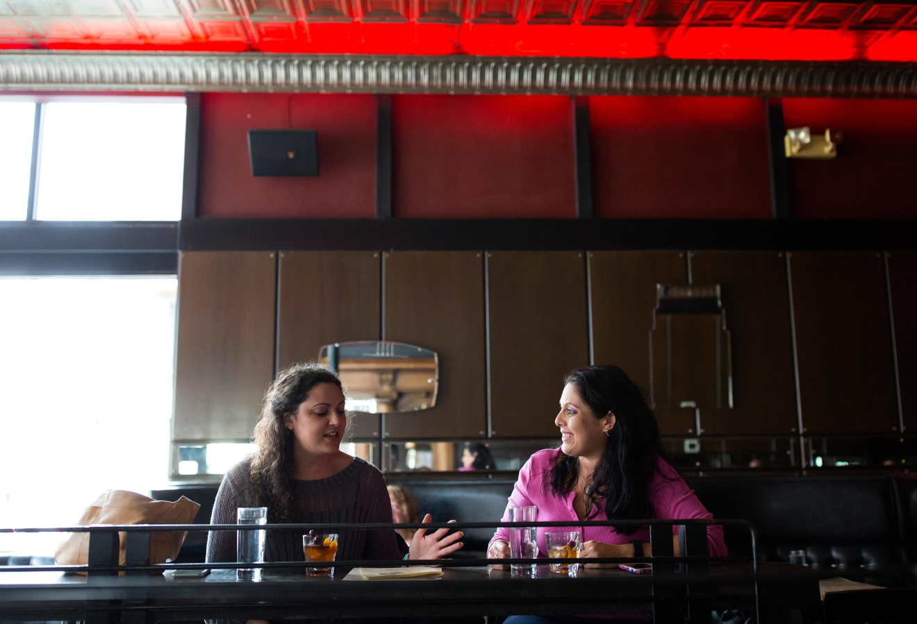 Anna Geisler, right, and Debi Scheenstra, chat over drinks as they visit Tini Bigs Lounge on its final day of business. (Sy Bean / Seattle Refined)