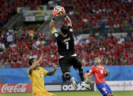 Chile's goalkeeper Claudio Bravo leaps above Australia's Tim Cahill to claim the ball during the group B World Cup soccer match between Chile and Australia at the Arena Pantanal in Cuiaba, Brazil, Friday, June 13, 2014.