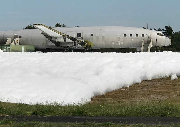 Foam covers the ground Monday morning surrounding a hangar at the Auburn-Lewiston Municipal Airport. (RUSS DILLINGHAM/SUN JOURNAL)