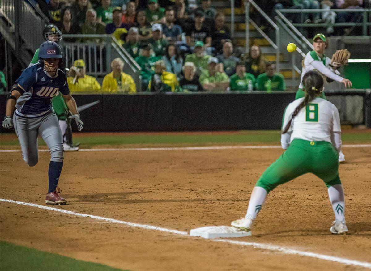 Oregon Ducks first base player Lauren Lindvall (#8) attempts to catch the ball for the out as Chicago Flames Lexi Watts (#1) runs to first. The No. 3 Oregon Ducks defeated the University of Illinois Chicago Flames 13-0 with the run-rule on Saturday night at Jane Sanders Stadium. The Ducks scored in every inning and then scored nine runs at the bottom of the fourth. The Oregon Ducks are now 22-0 in NCAA regional games. The Oregon Ducks play Wisconsin next on Saturday, May 20 at 2pm at Jane Sanders Stadium. Photo by Cheyenne Thorpe, Oregon News Lab
