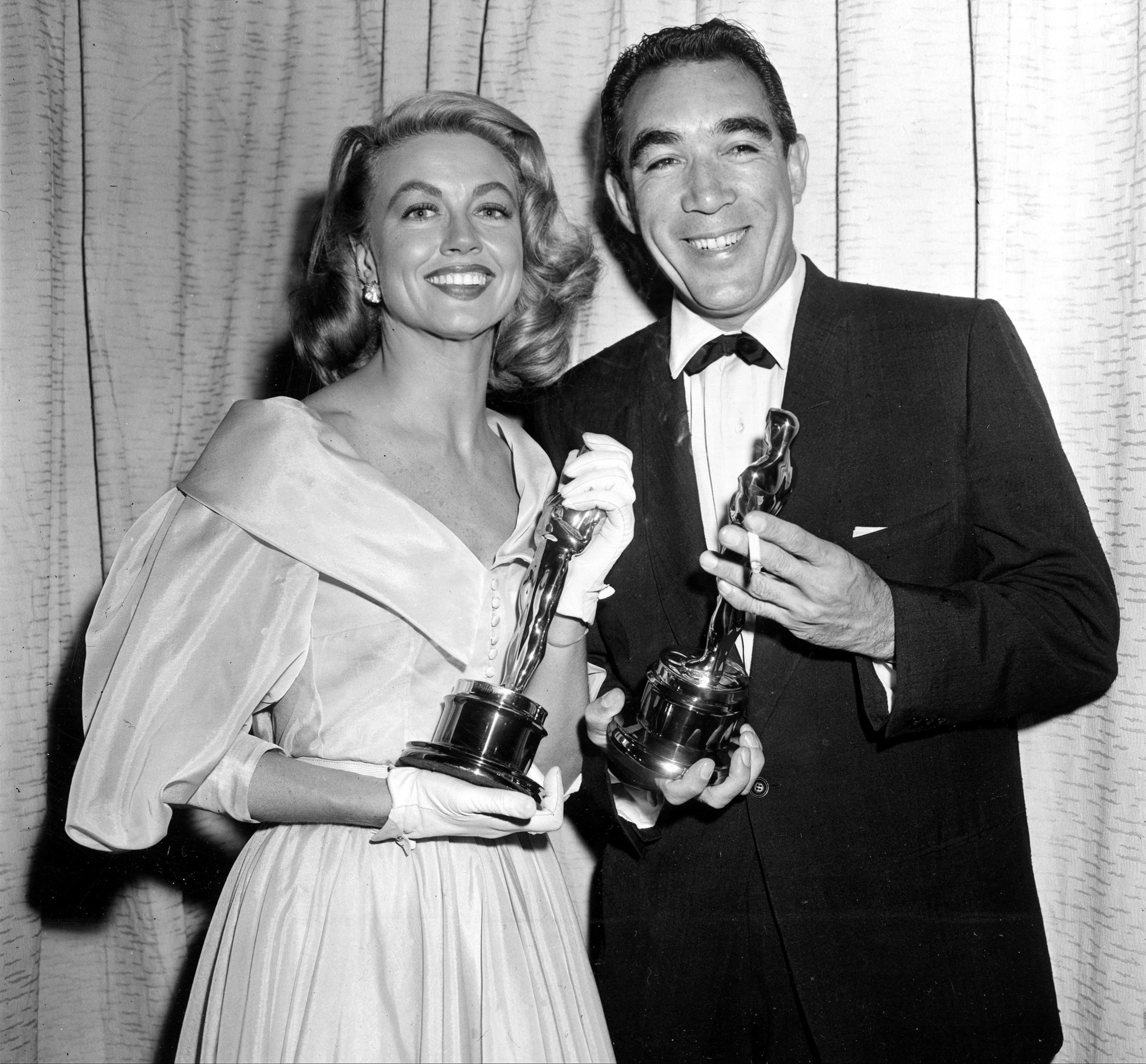 "File-This March 27, 1957, file photo shows Best supporting Oscar winners Dorothy Malone and Anthony Quinn posing at the Academy Awards in Hollywood, Calif. Malone, who won hearts of 1960s television viewers as the long-suffering mother in the nighttime soap ""Peyton Place,"" has died. Her daughter Mimi Vanderstraaten says Malone died Friday, Jan. 19, 2018, from natural causes in her hometown of Dallas. She was 93. (AP Photo, File)"