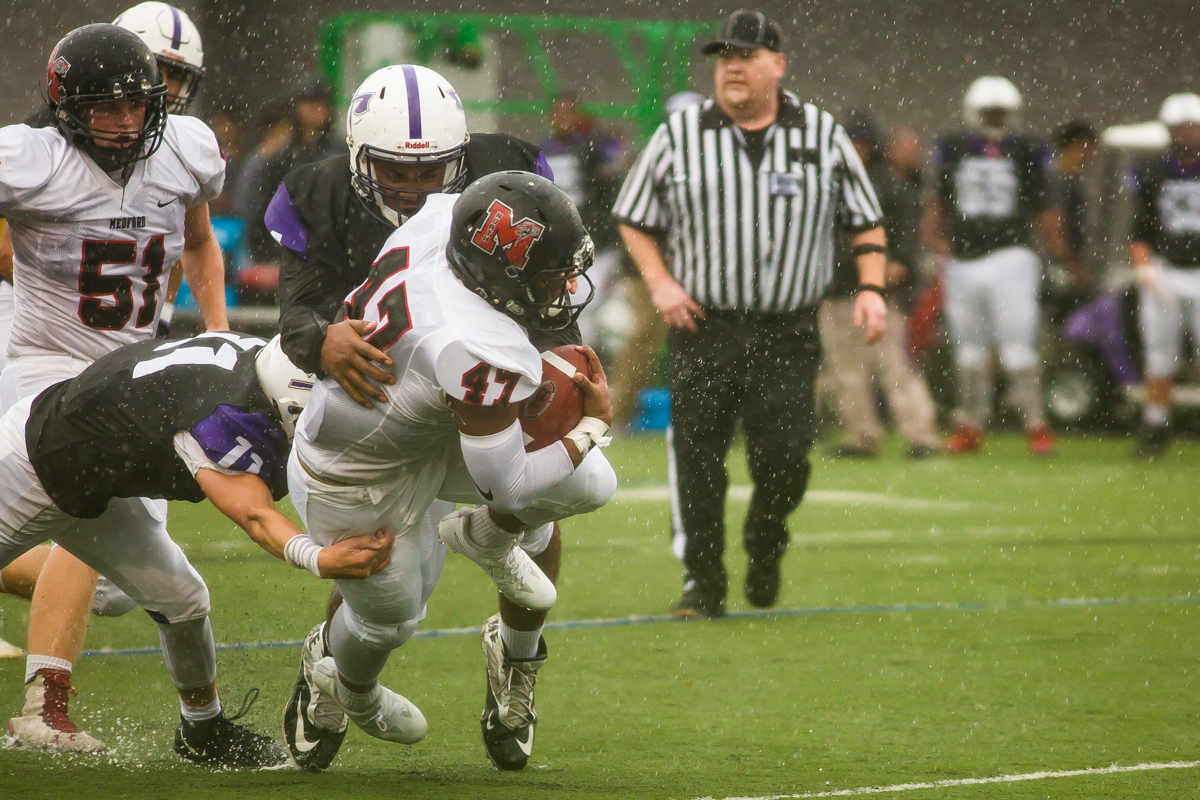 North Medford running back Isaac Manuel (#47) fights through rain and South Eugene defenders on his way downfield. The game had been postponed from Friday due to unhealthy levels of smoke in the atmosphere due to nearby forest fires. Photo by Dillon Vibes